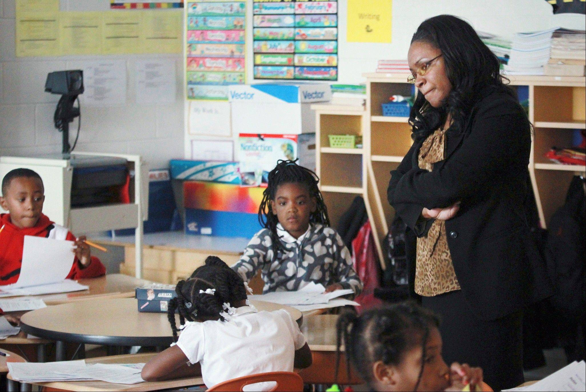 Dunbar Elementary School Principal Carlynda Coleman watches second-grade students fill in charts tracking their progress in East St. louis, Ill.