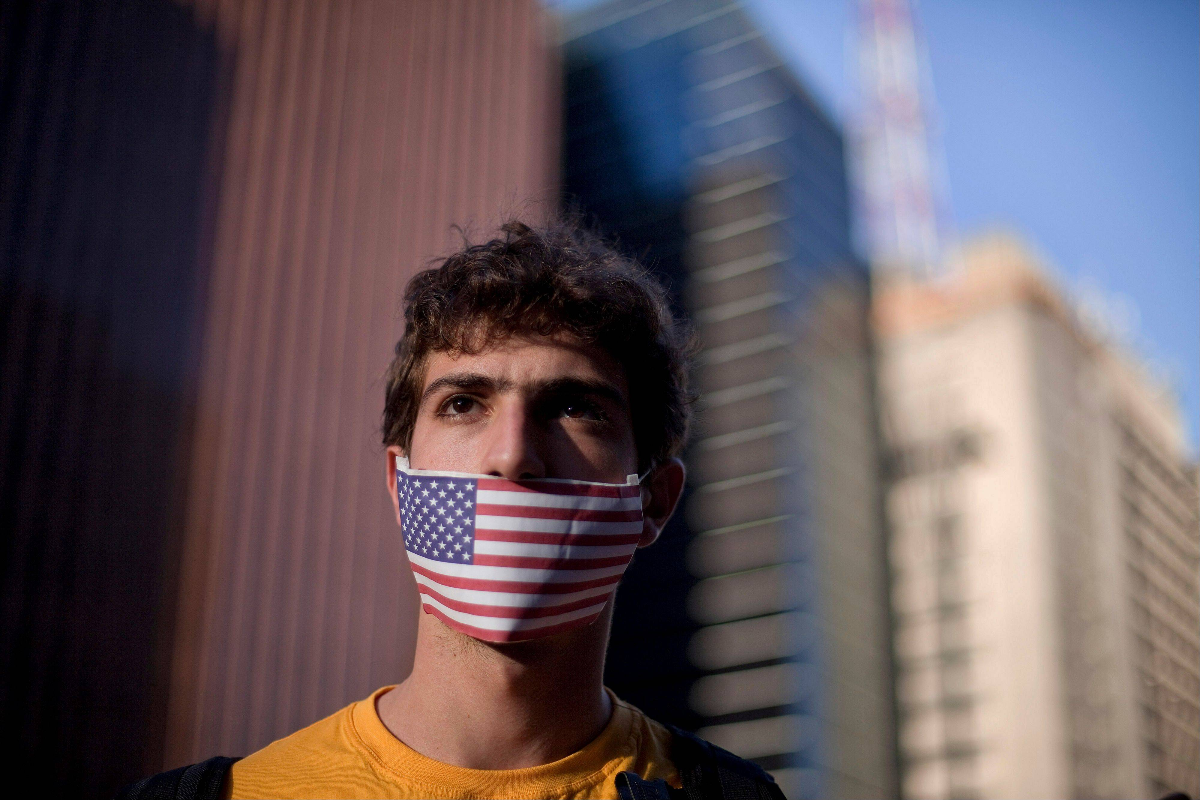 A protester wearing a U.S. flag over his mouth demonstrates with others in Sao Paulo, Brazil on Thursday, July 18, 2013 against their government�s rejection of the asylum application of U.S. citizen Edward Snowden who leaked top-secret documents about sweeping U.S. surveillance programs. Former U.S. secretary of state Madeleine Albright once dubbed the United States �the indispensable nation.� But the world watched America stumble through a string of crises in 2013.