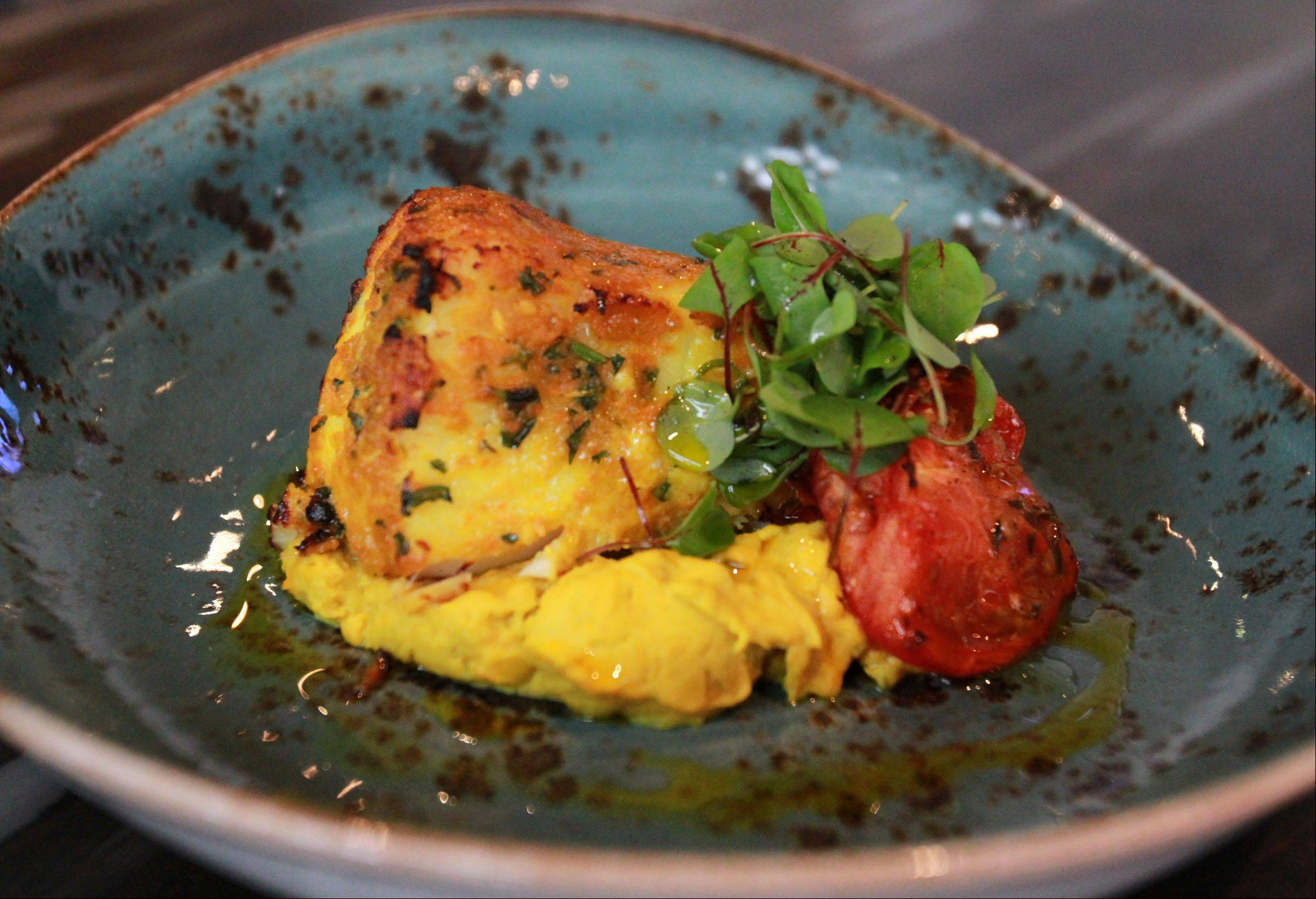 Malay spiced sea bass rests on a bed of curried cauliflower and potato pur�e at e+o Food and Drink at Randhurst Village in Mount Prospect.