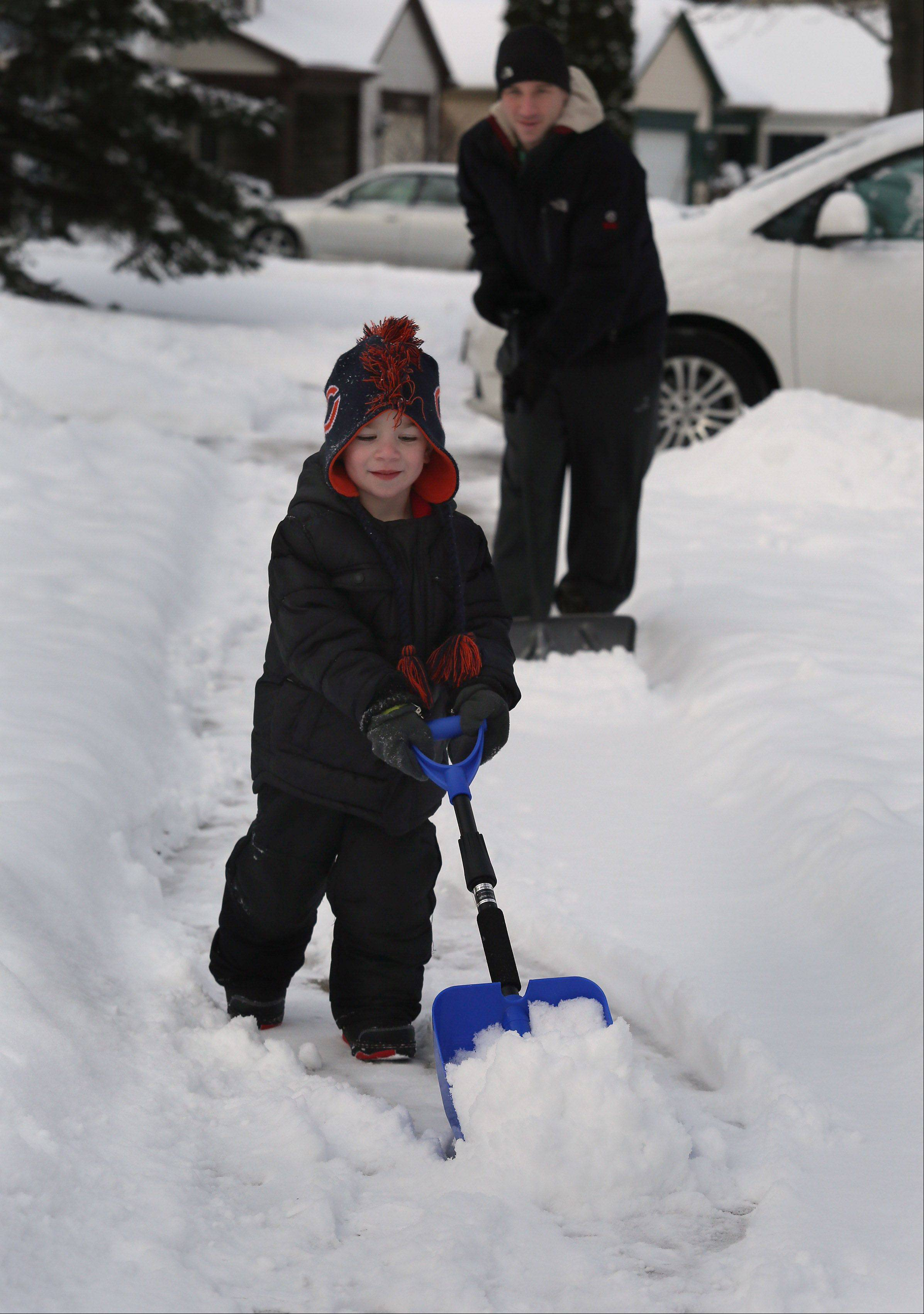 Three-year-old Mason Freed and his dad, Jordan, of Mundelein shovel the sidewalk after overnight snows blanketed the area. Mason was happy to help after getting a new Bears hat and a small-size snow shovel recently.