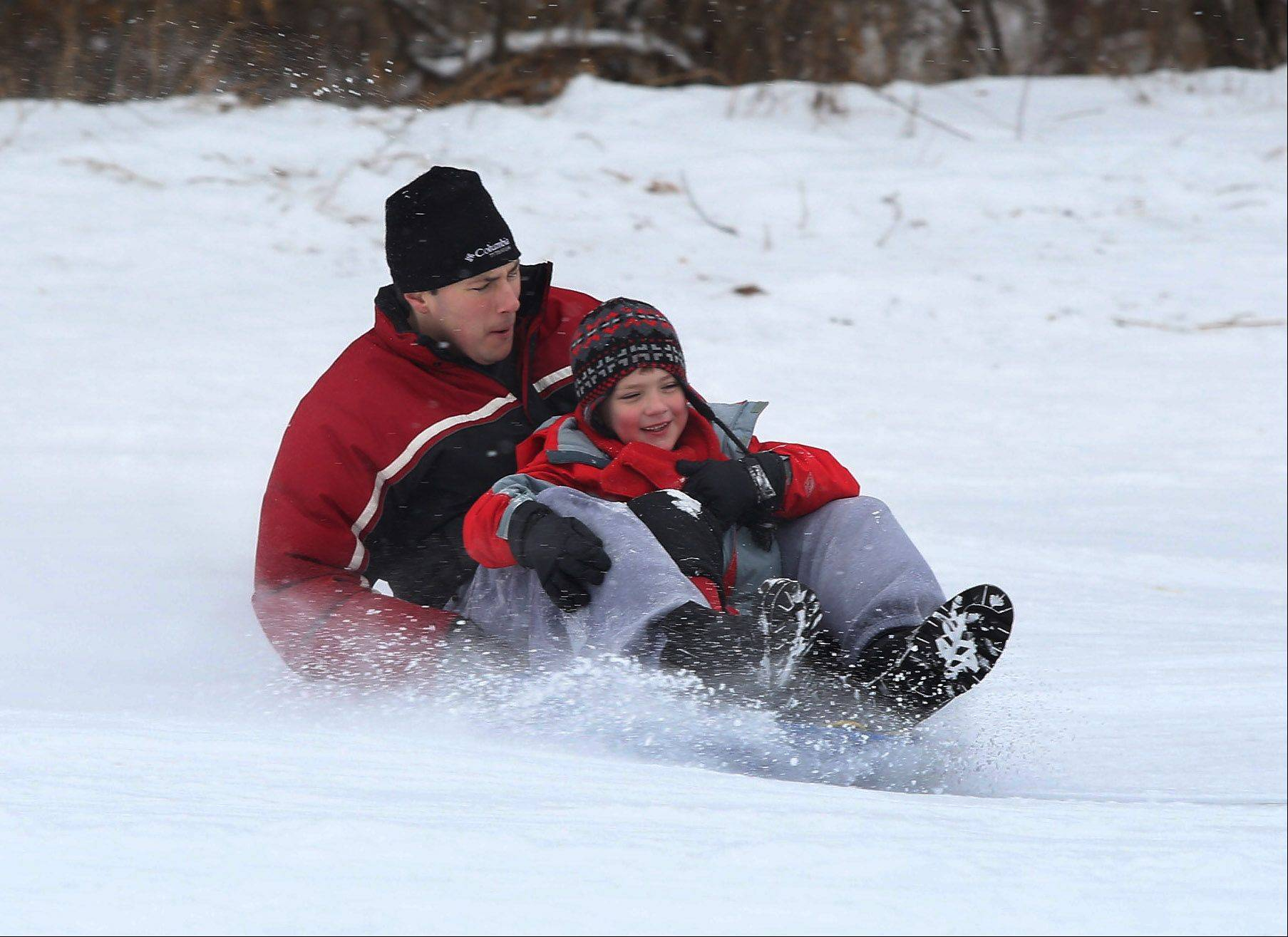 Jesse Walker of Libertyville sleds down the hill with his son, Joey, 7, at Adler Park in Libertyville on Thursday. The park features two sledding hills, an ice rink and a warming house during the winter months.