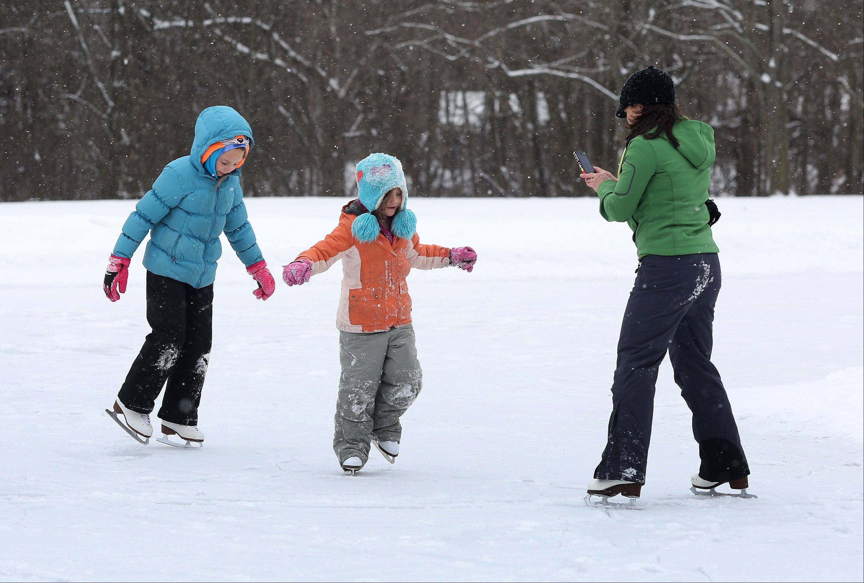Libertyville resident Robin Frey videotapes her daughters, Jillian, 6, and Emaline, 9, while they ice skate at Adler Park in Libertyville on Thursday.