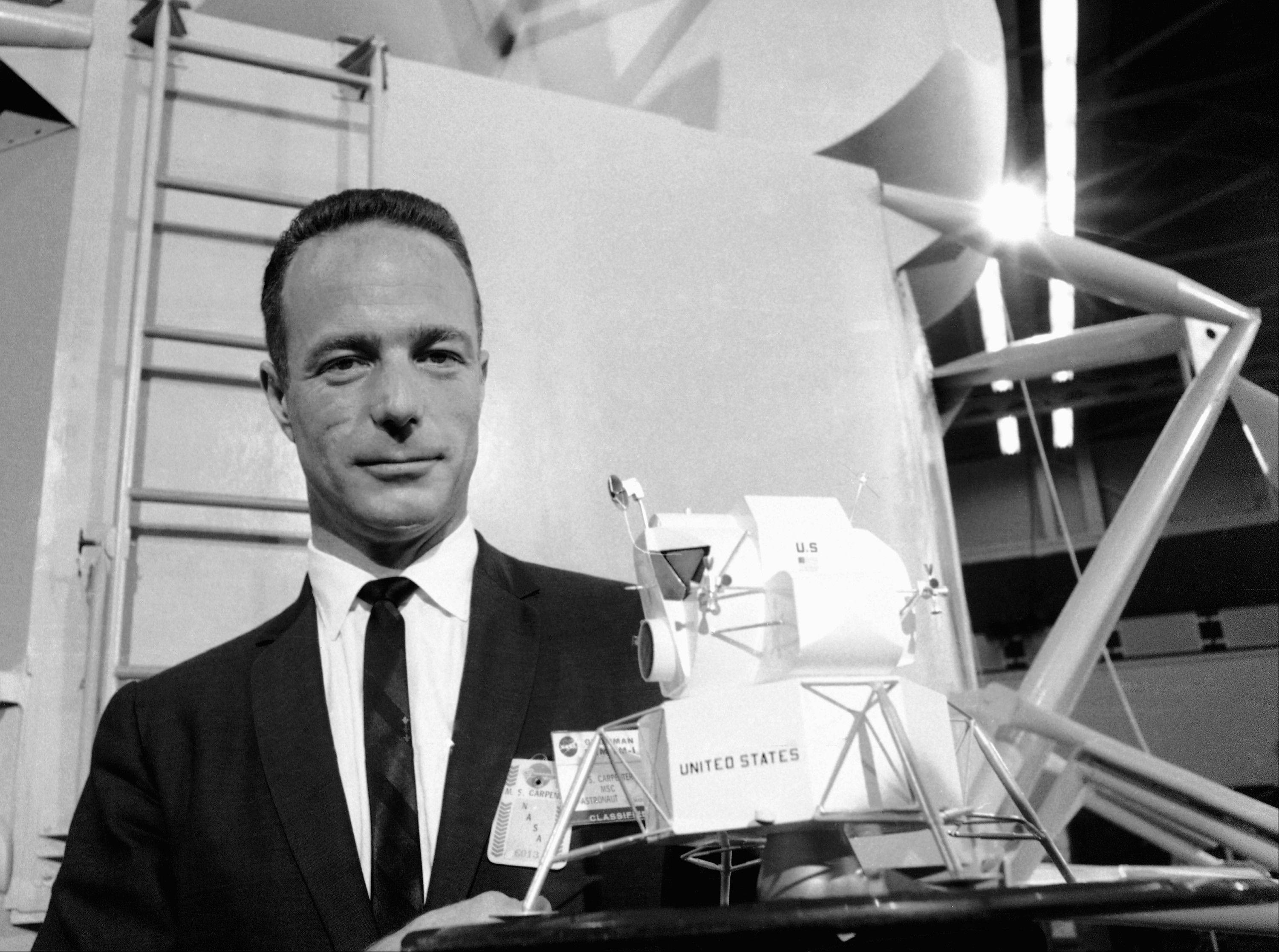 In this March 26, 1967 file photo, astronaut Scott Carpenter poses with model of the Lunar Excursion Module (LEM) at Grumman Aircraft Engineering Corp. plant in Bethpage, N.Y. Carpenter, the second American to orbit the Earth and first person to explore both the heights of space and depths of the ocean, died Thursday, Oct. 10, 2013 after a stroke. He was 88.