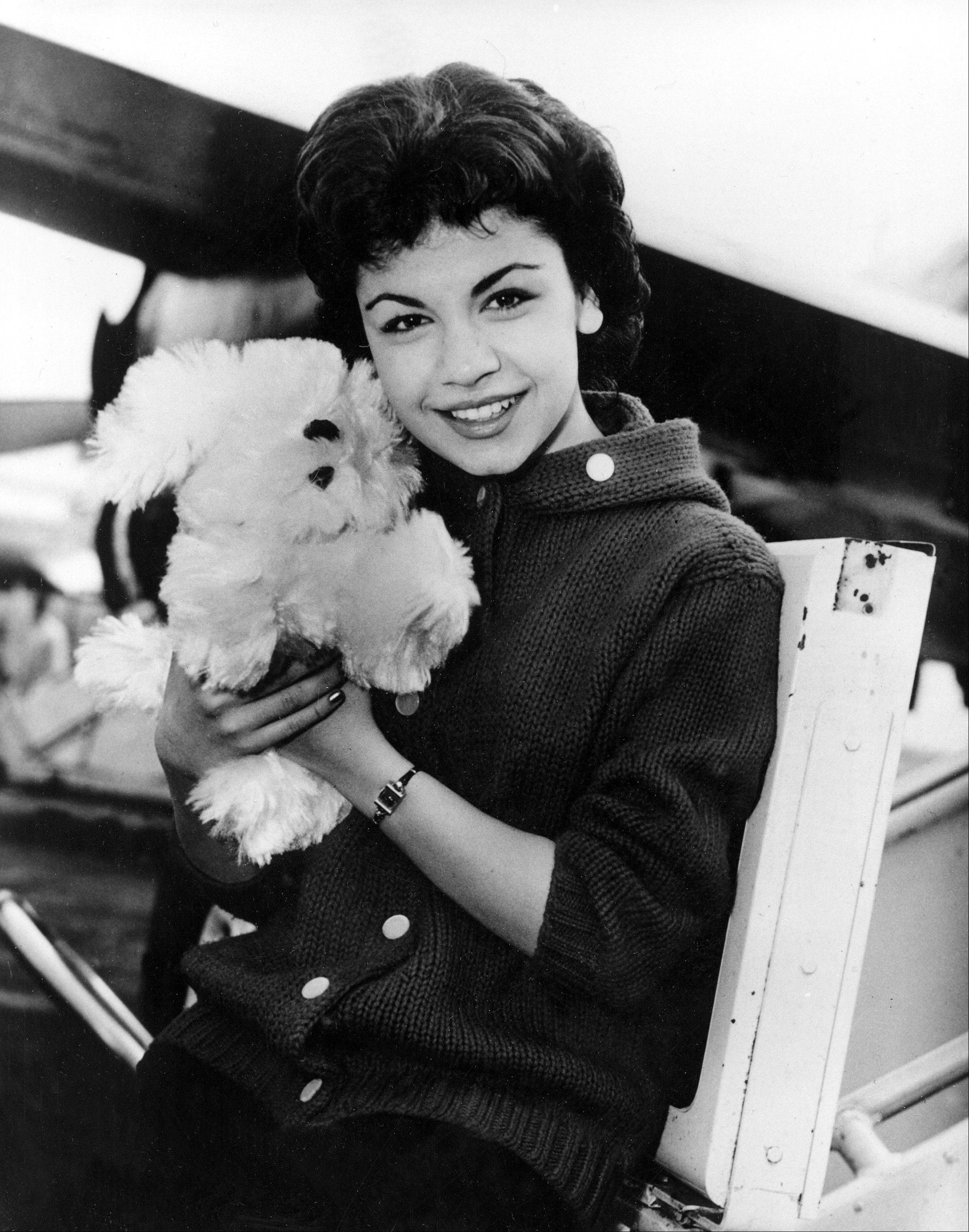 In this March 24, 1959 file photo, 16-year-old Annette Funicello poses with her Shaggy Dog doll, at Idlewild Airport in New York. Funicello, also known for her beach movies with Frankie Avalon, died April 8, 2013 at age 70.