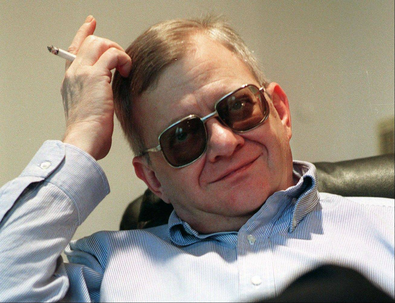 In this Feb. 4, 1998 file photo, writer Tom Clancy sits in his home in Calvert County, Md. Clancy, the best-selling author of more than 25 fiction and nonfiction books for the Penguin Group, died on Oct. 1, 2013 in Baltimore. He was 66.
