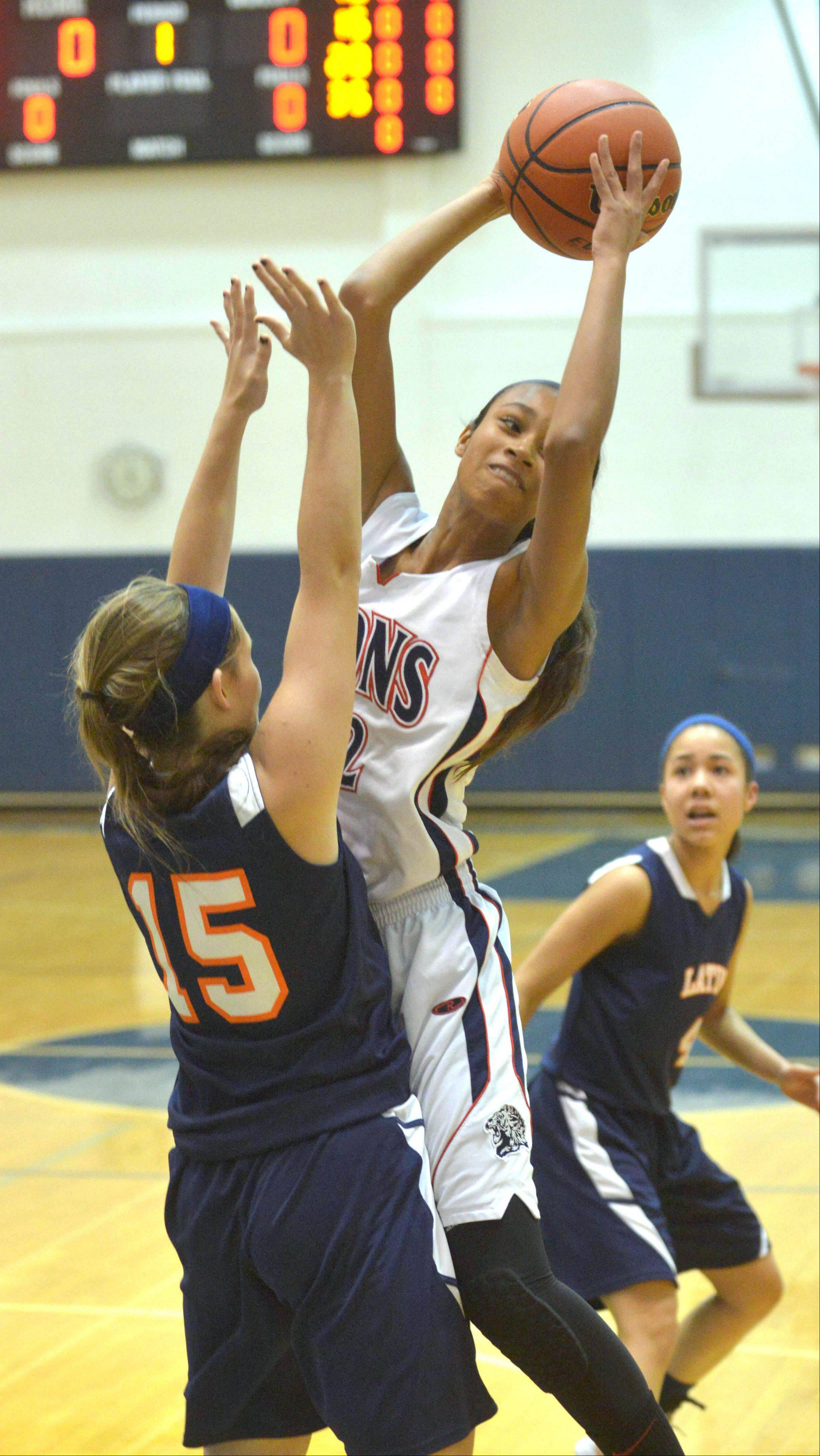 Tyann Legrand-Melton takes a shot over Jen Costa of Latin during the Latin at Lisle girls basketball game Thursday.