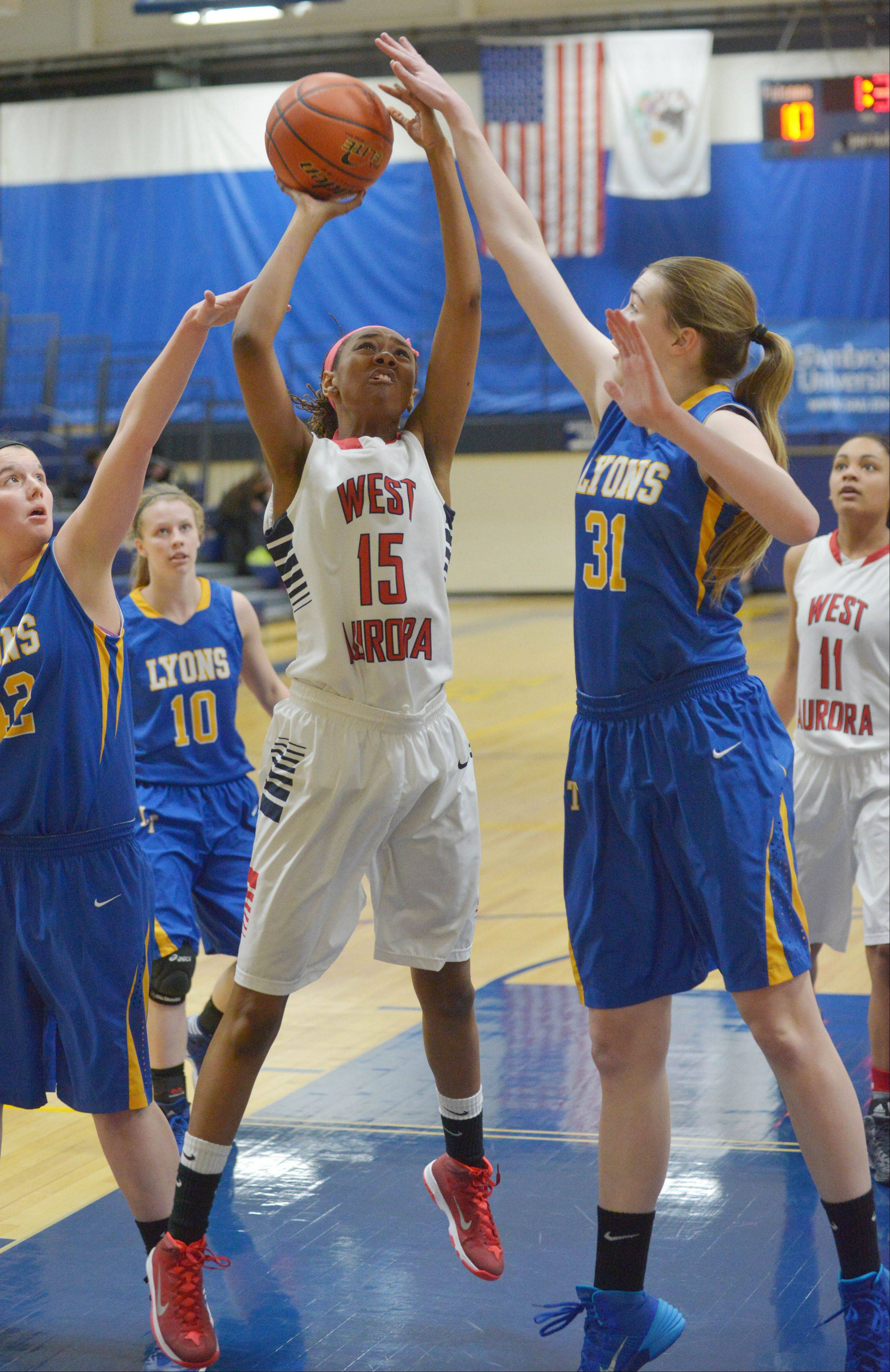Natalee DeJohnette, of West Aurora, puts up a shot while Emily Pender, of Lyons, attempts to block during the West Aurora at Wheaton North girls basketball tournament game Thursday.