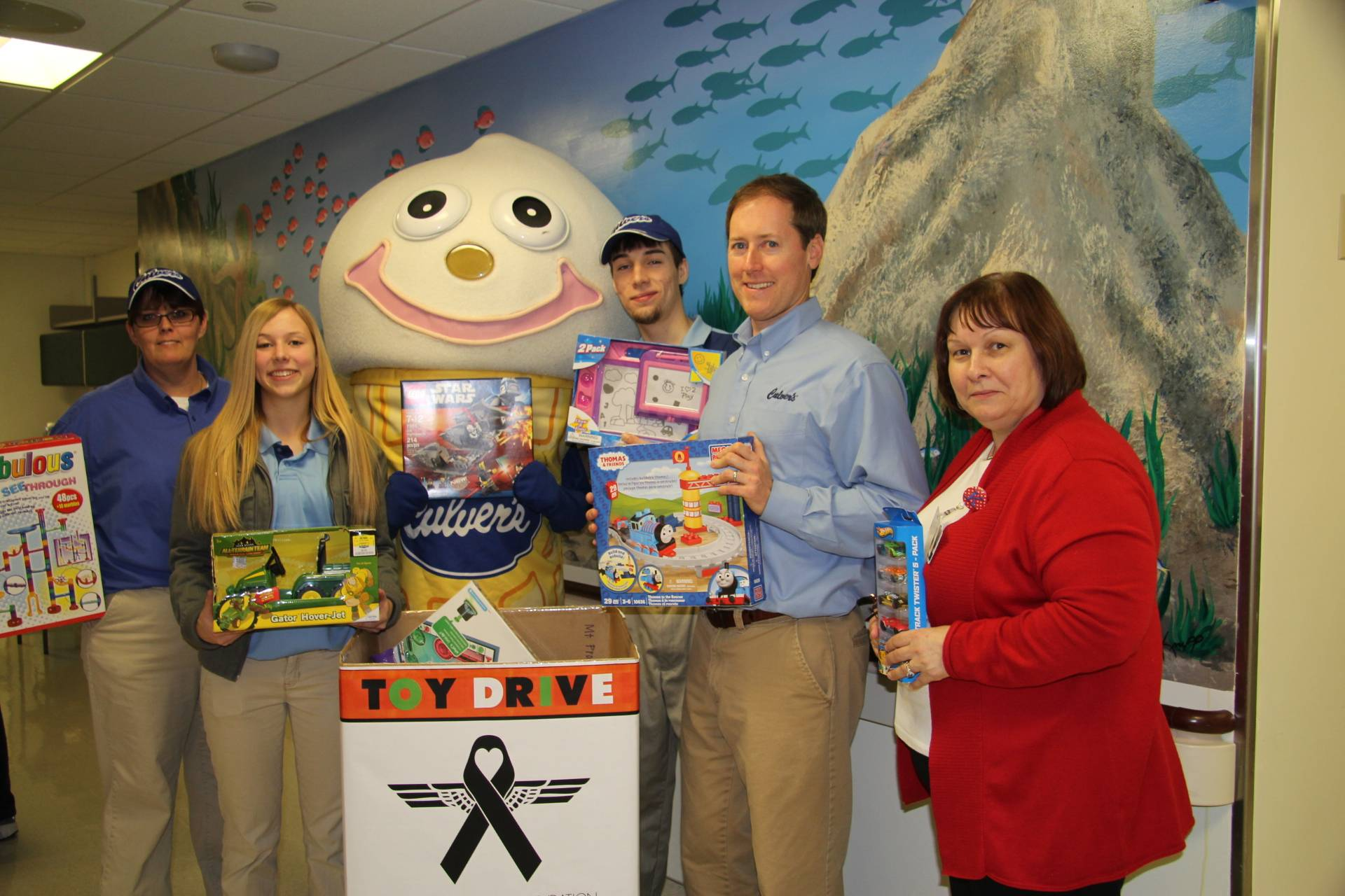Scoopie shows off some donated toys with (L to R) Arlington Heights manager Lisa Sayeh, Team Members Alisa Kaiser and Dylan Youngs, Culver's of Buffalo Grove owner Kevin Weasler and Pediatrics Manager Karen Lepucki.