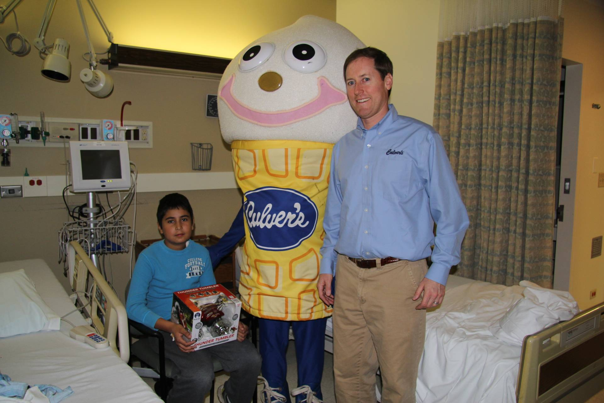 Culver's of Buffalo Grove owner Kevin Weasler helps Scoopie deliver a special toy for 11-year-old David Vargas at Northwest Community Hospital.