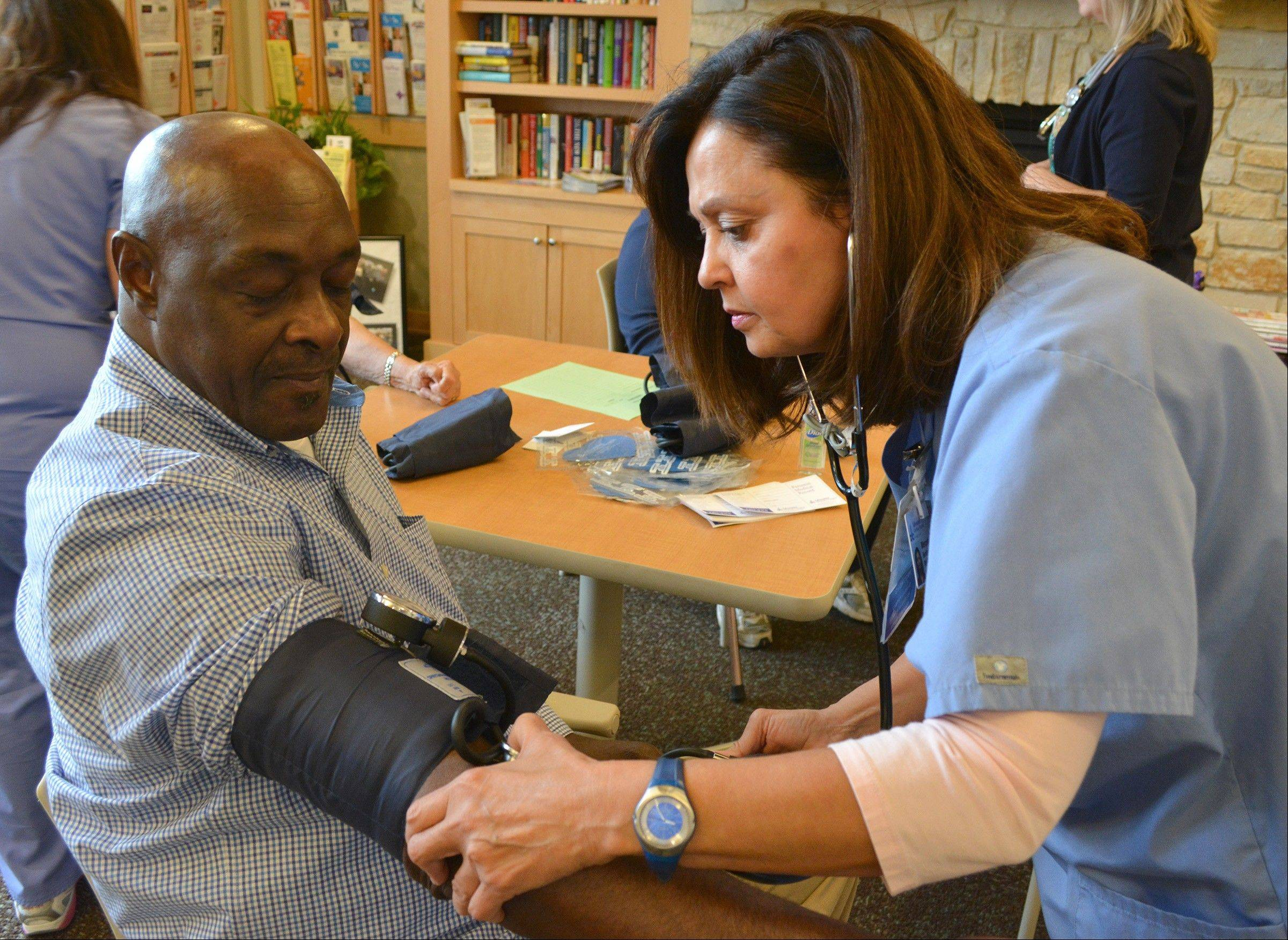 Joseph Lee of Glendale Heights has his blood pressure checked by Adventist GlenOaks Hospital registered nurse Mercedes Bentley. The hospital offers free blood pressure checks monthly at the Glendale Heights Center for Senior Citizens.