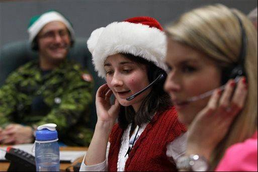 In this Dec. 24, 2012 photo, volunteer Katherine Beaupre takes phone calls from children asking where Santa is and when he will deliver presents to their house,during the annual NORAD Tracks Santa Operation, at the North American Aerospace Defense Command, or NORAD, at Peterson Air Force Base, in Colorado Springs, Colo.