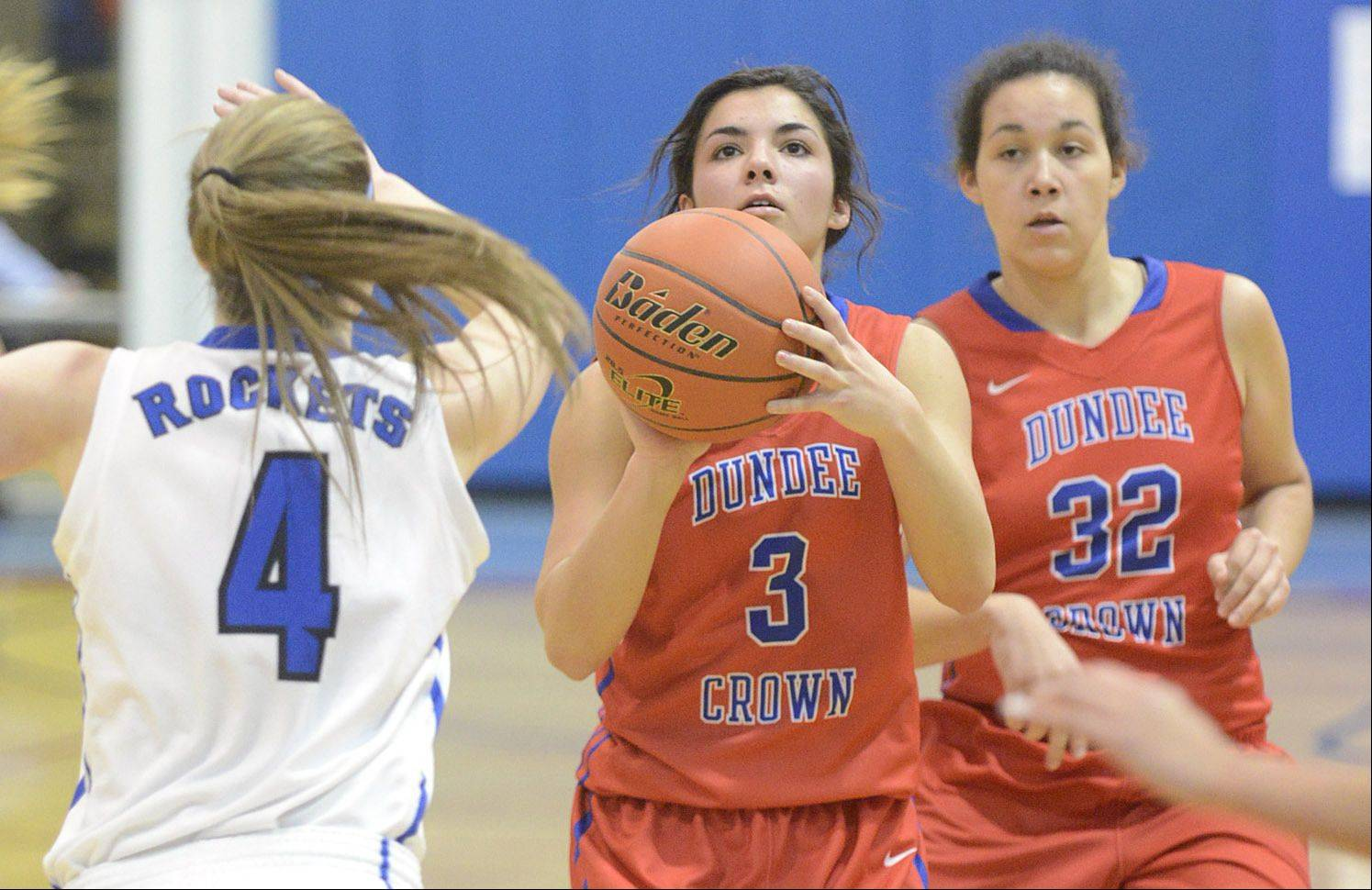 Burlington Central's Kayla Ross attempts to block a shot by Dundee-Crown's Francesca Scarpelli in the second quarter on Friday, December 27. Dundee-Crown's Jesania Laboy on right.