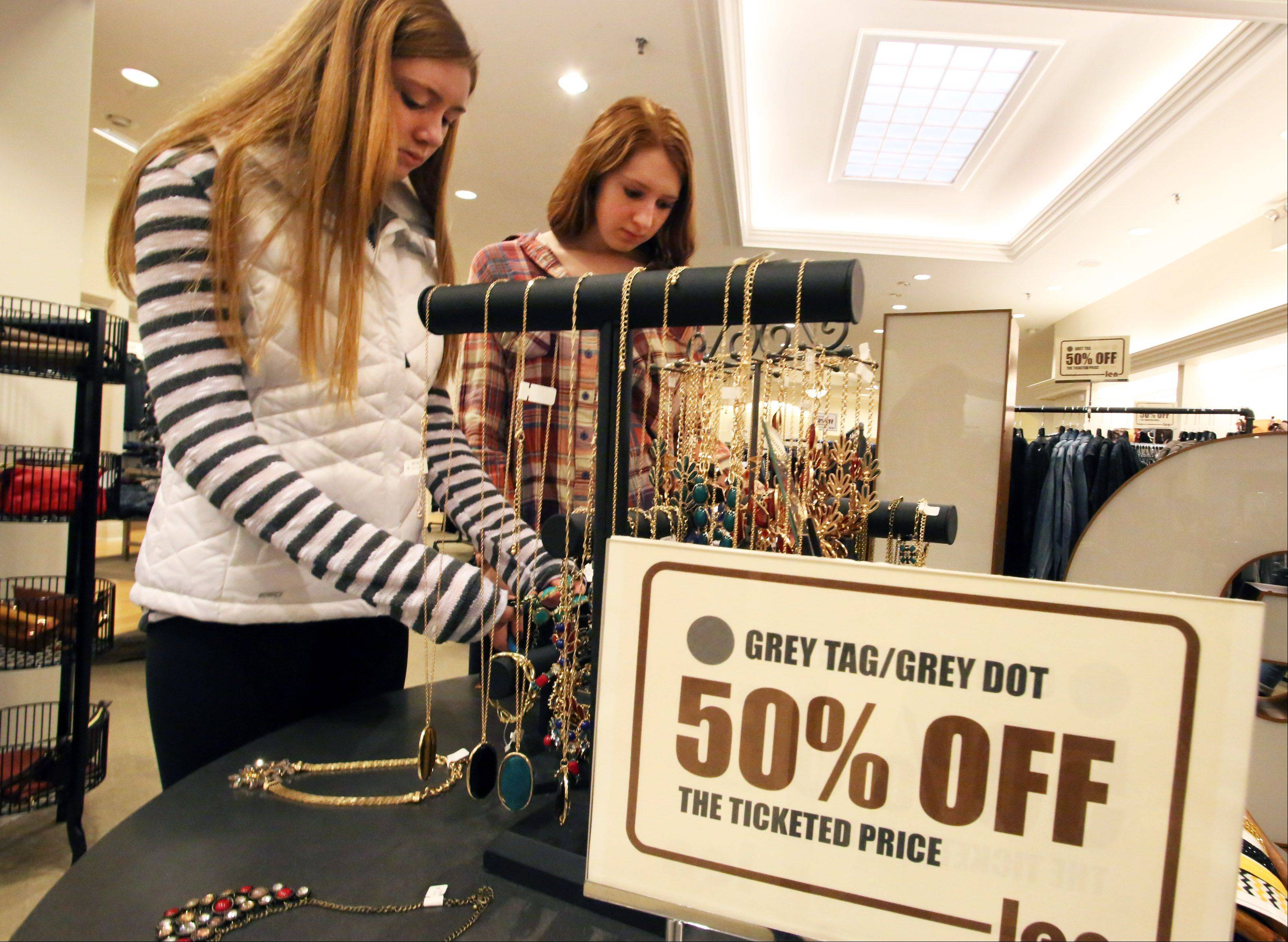 Jesse Cumpher, 14, and her sister Morgan Cumpher, 17, check out half-priced jewelry at Len in Woodfield Mall Friday.