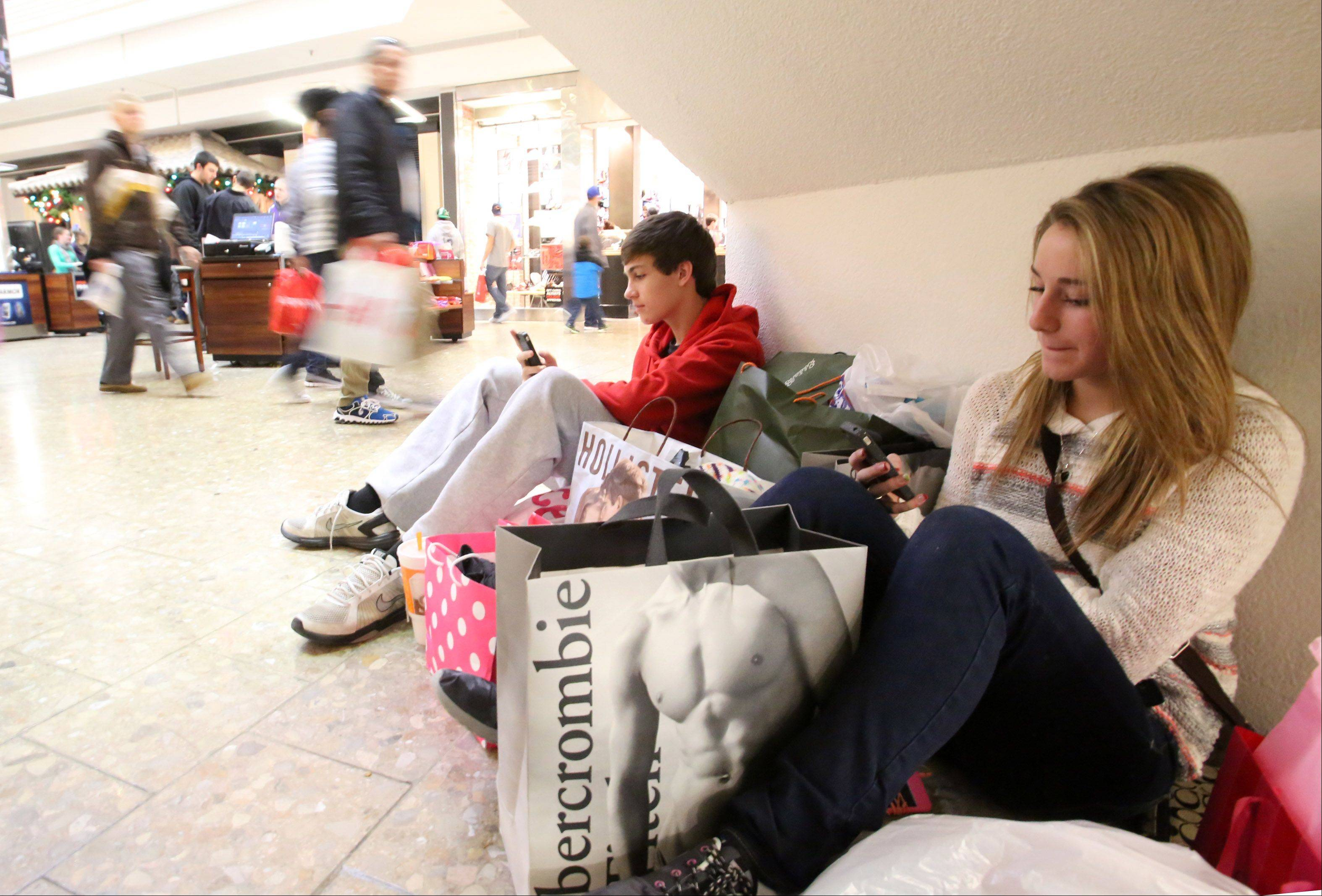 Sydney Keckeisen and her cousin Riley Keckeisen, both 14 of Kenosha, Wis., take a break from shopping under a staircase at Woodfield Mall in Schaumburg Friday.
