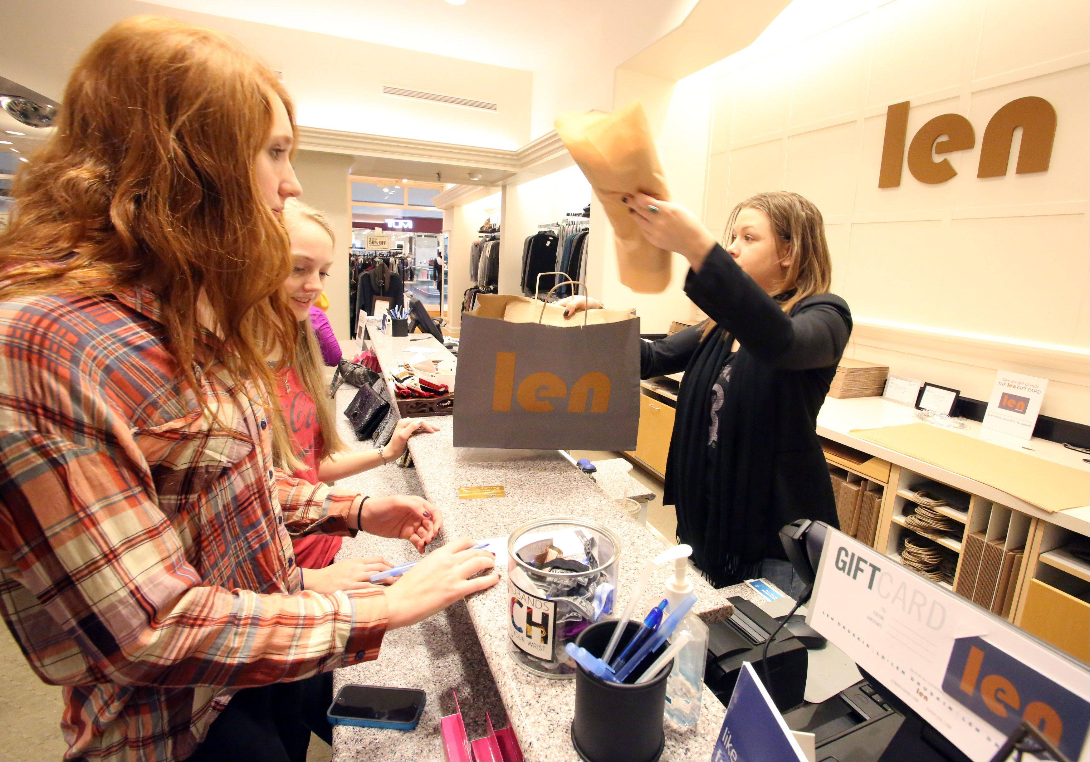 Morgan Cumpher, 17, foreground, and Emily Bloom, 16, left, purchase clothing items from sales representative Aimee Kriegl Friday at Len at Woodfield Mall in Schaumburg.
