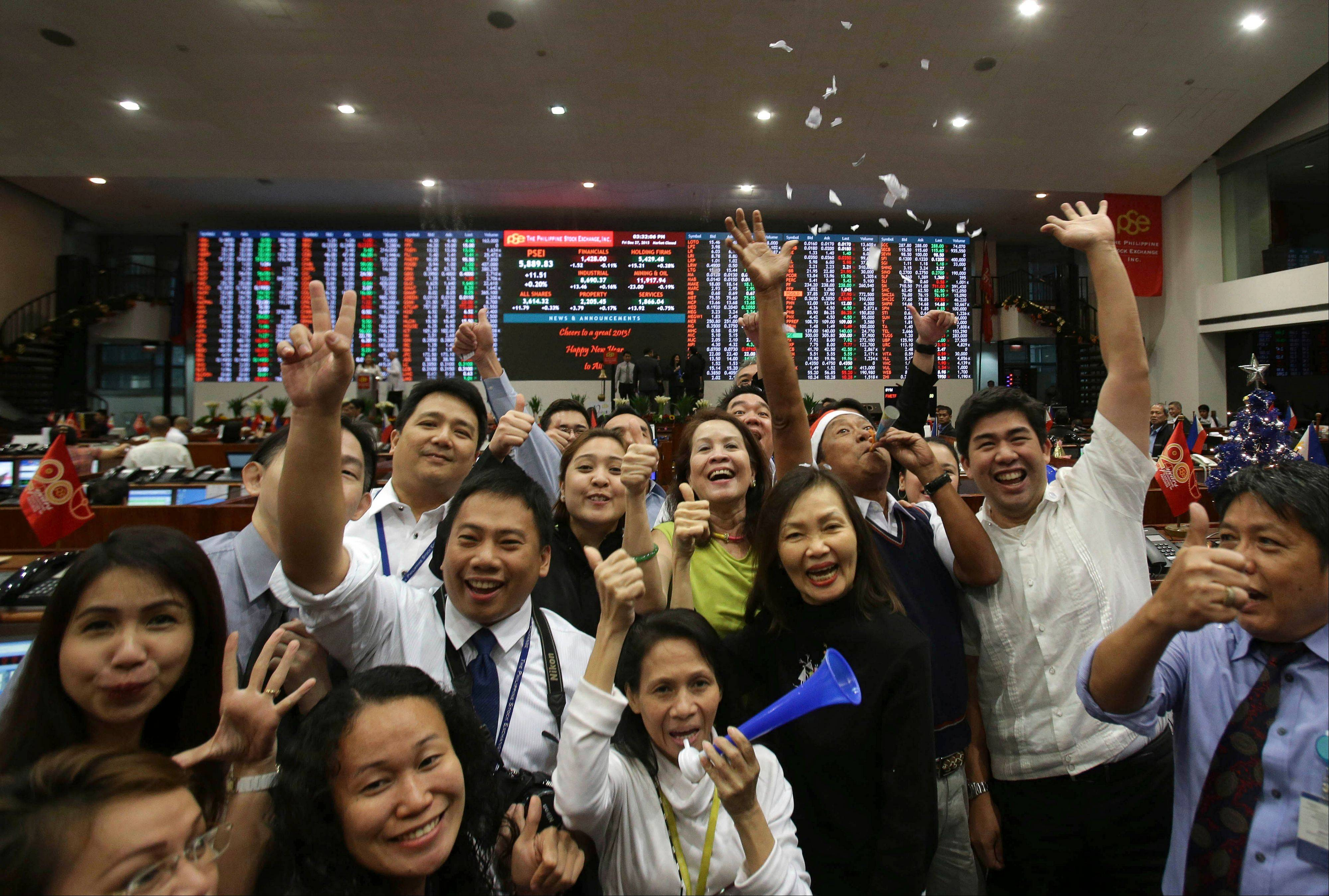 Filipino traders cheer in front of the electronic board Friday during the last day of trading this year at the Philippine Stock Exchange in the financial district of Makati, south of Manila, Philippines. The Philippine Stock Exchange index rose to a record high of 7,403.65.