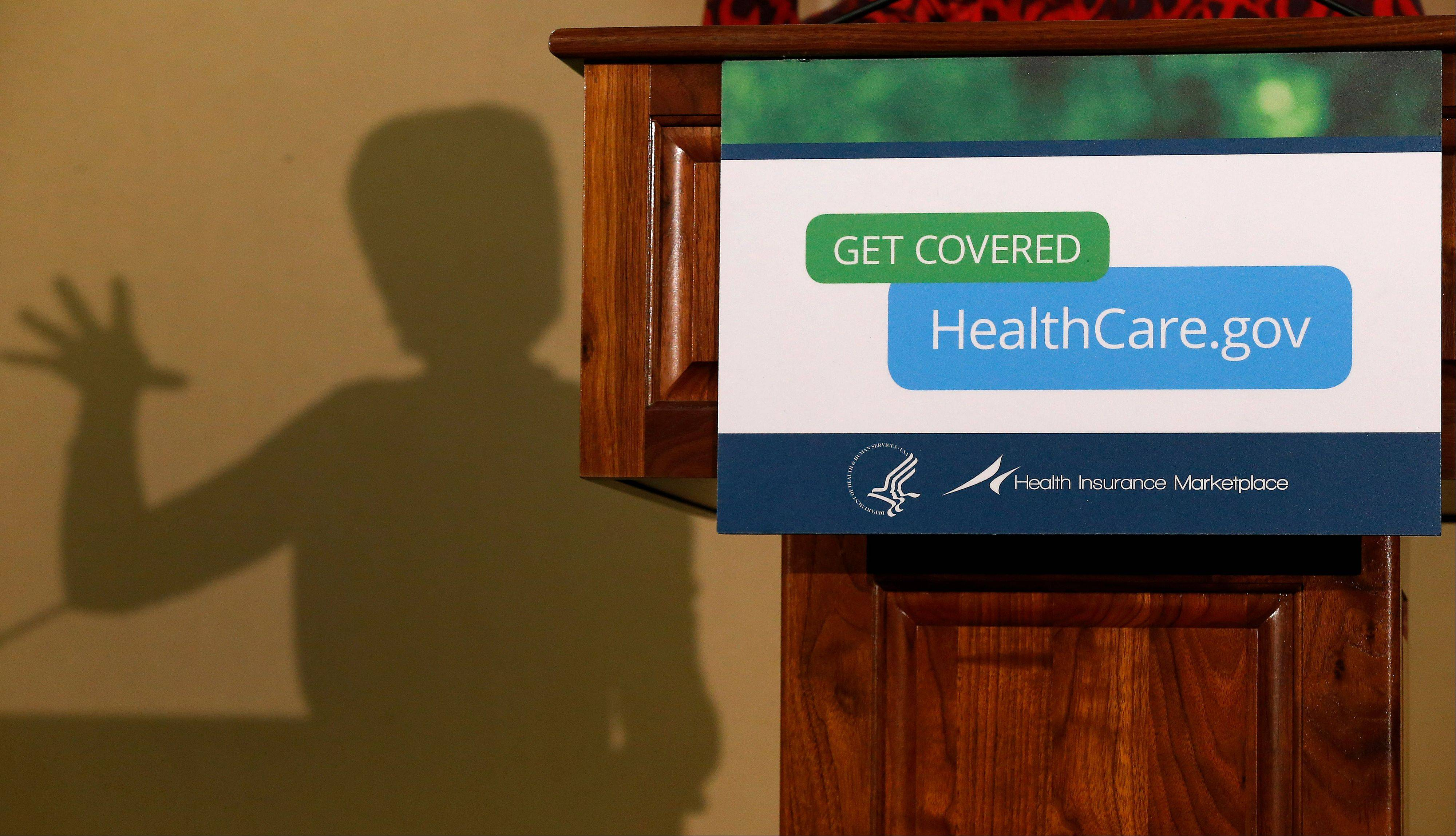 The shadow of Health and Human Services Secretary Kathleen Sebelius is cast on a wall as she speaks at the Community Health and Social Services Center in Detroit. A month after President Barack Obama announced people could keep insurance policies slated for cancellation under the federal health overhaul, the reversal has gotten a mixed response from insurers, state regulators and consumers.
