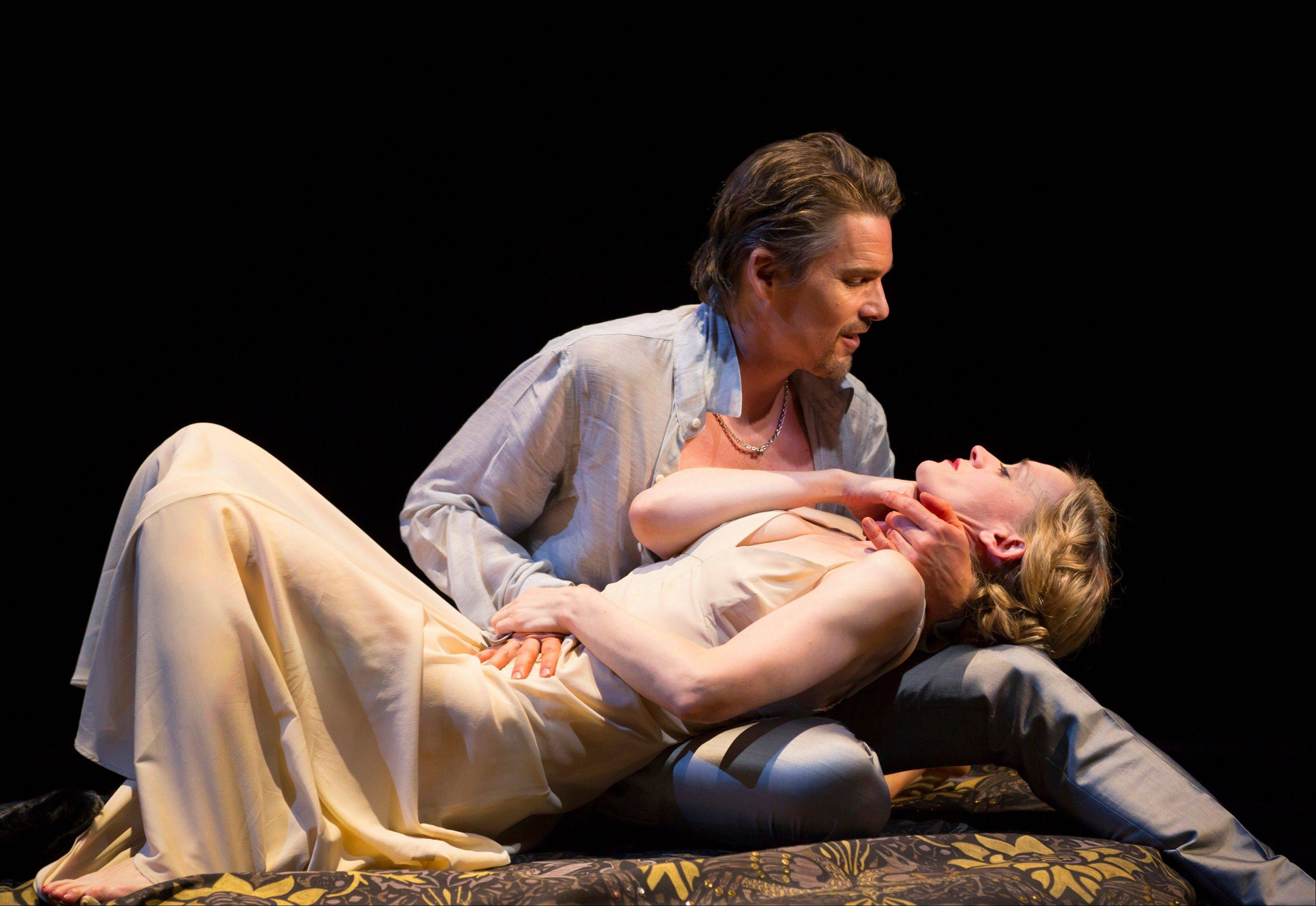 "This image released by Lincoln Center Theater shows Ethan Hawke and Anne-Marie Duff during a performance of ""Macbeth, in New York. Scott Pask's sets include giant movable slabs, a vase of flowers that suddenly loses its petals and a bright, airy, leaf-covered canopy. Japhy Weideman's stunning lighting turns everyone into rock gods. And Catherine Zuber's timeless, ultrasexy costumes make everyone gorgeous."