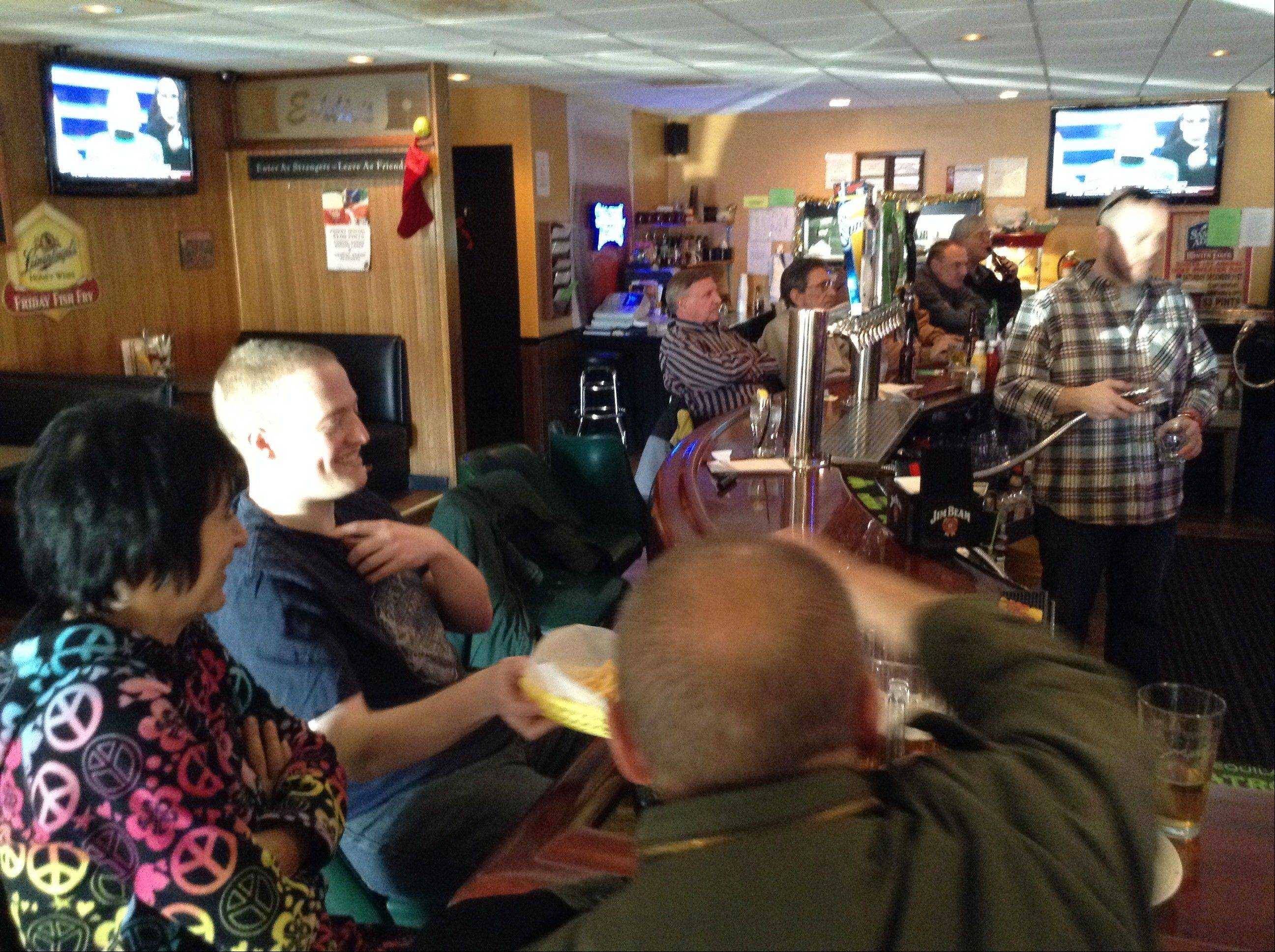 "Jerry Slowik of Arlington Heights gathers with his parents, Debbie and Jerry Sr., and other avid ""Jeopardy!"" watchers Friday afternoon at Eddie's bar to watch his day two appearance on the game show."