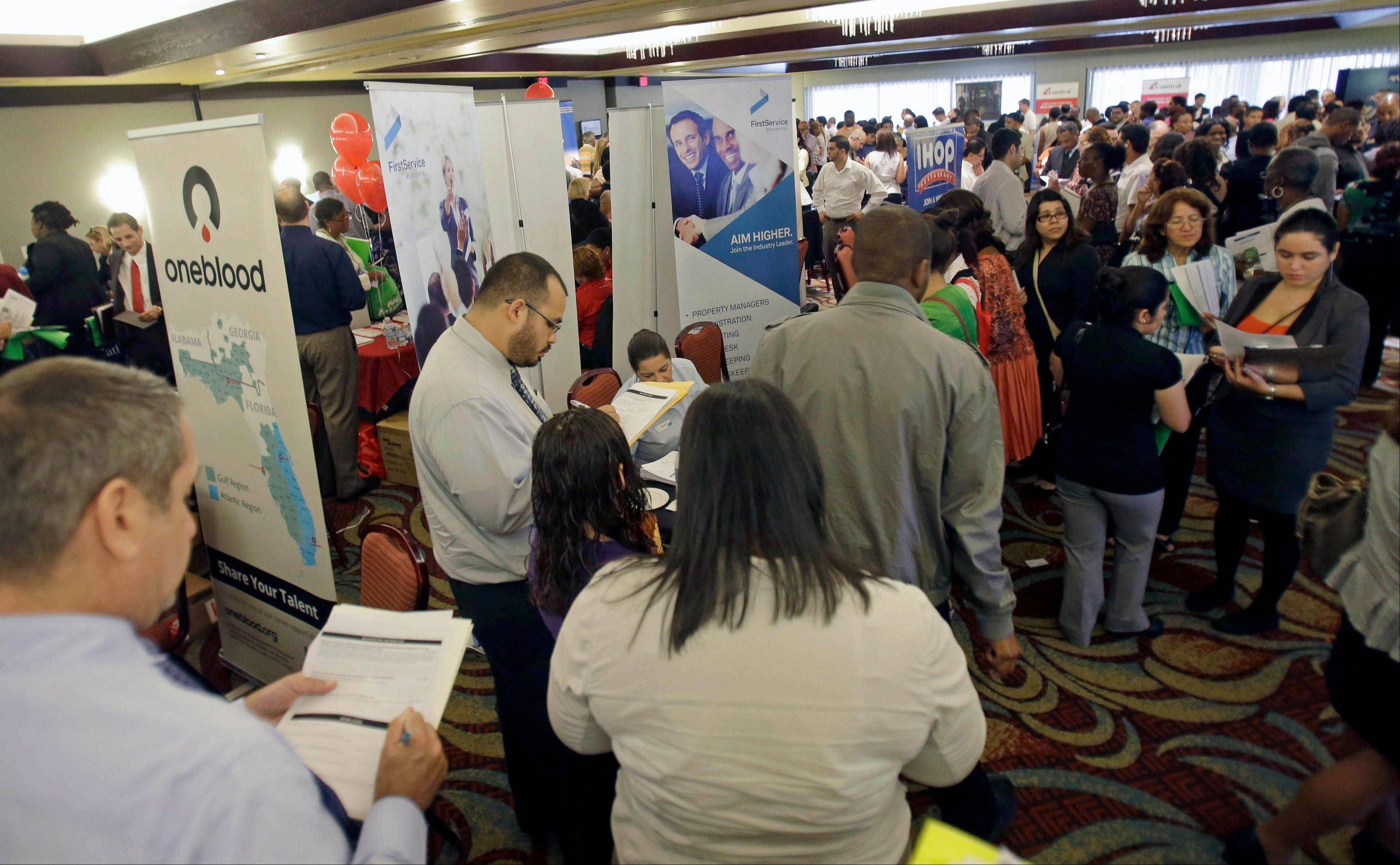 Job seekers check out companies at a job fair in Miami Lakes, Fla. More than 1 million Americans are bracing for a harrowing, post-Christmas jolt as federal unemployment benefits come to a sudden halt this weekend.