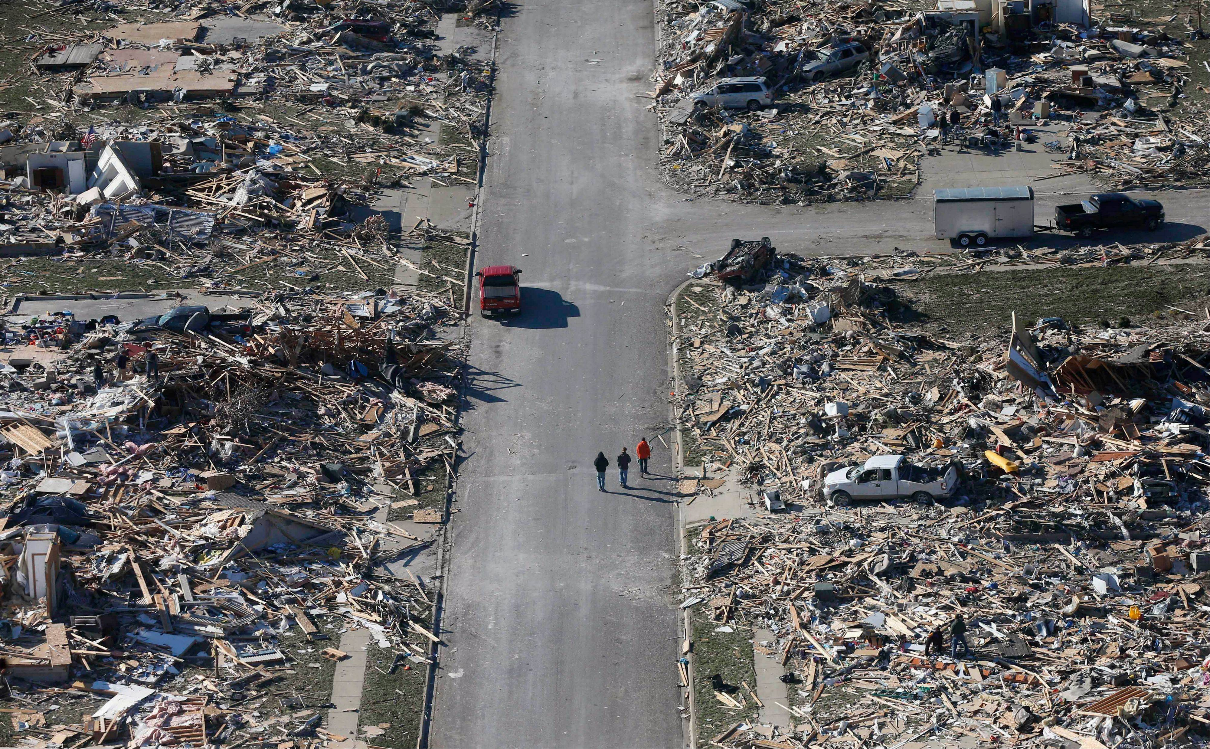 This Monday, Nov. 18, 2013 aerial file photo shows people walking down a street where homes once stood that were destroyed by a tornado that hit the western Illinois town of Washington. Two dozen tornadoes swept through the state killing seven people. It was voted as one of the top 10 stories in Illinois for 2013.