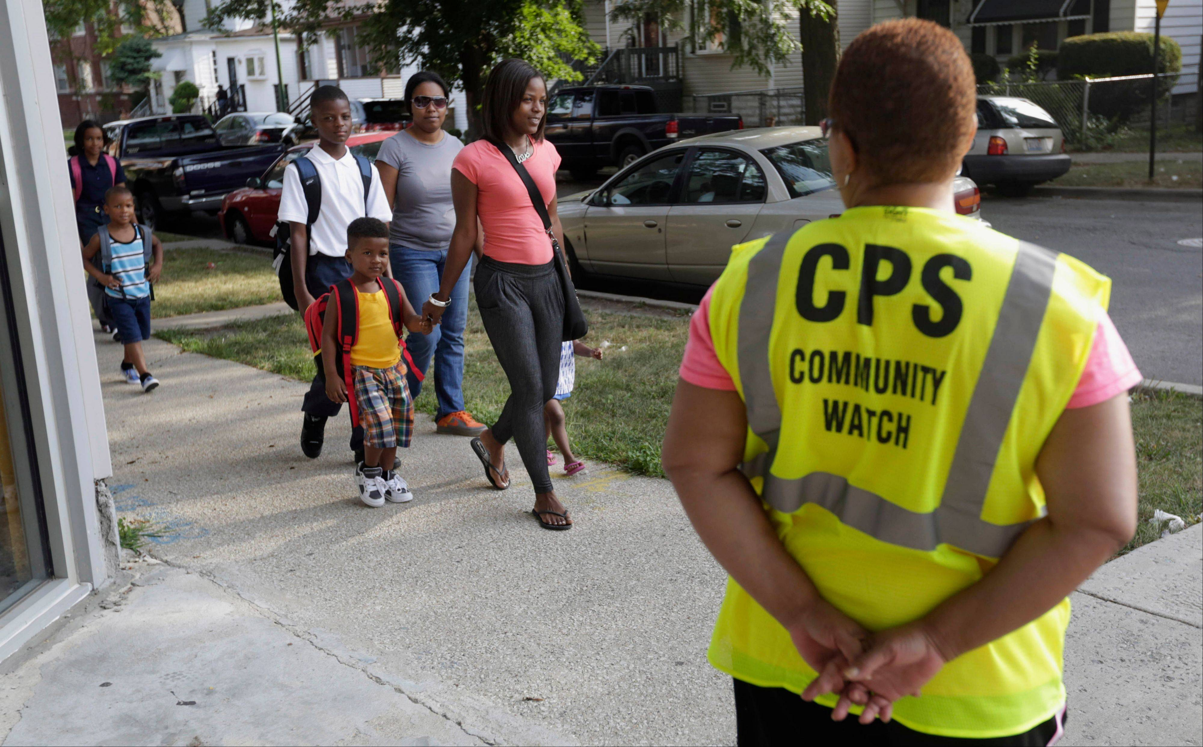"In this Aug. 26, 2013 file photo, safety guard Renee Green watches as parents walk with their children on the first day of school in Chicago. The Chicago Public Schools announced in May it would close about 50 schools and programs to deal with a budget deficit and lower attendance numbers, The closures forced many children to walk designated ""Safe Passage"" routes possibly crossing through gang boundaries to get to a new school. The ambitious plan sparked protests and lawsuits and could help define _ for better or worse _ Mayor Rahm Emanuel's term in office. It was voted as one of the top 10 stories in Illinois for 2013."