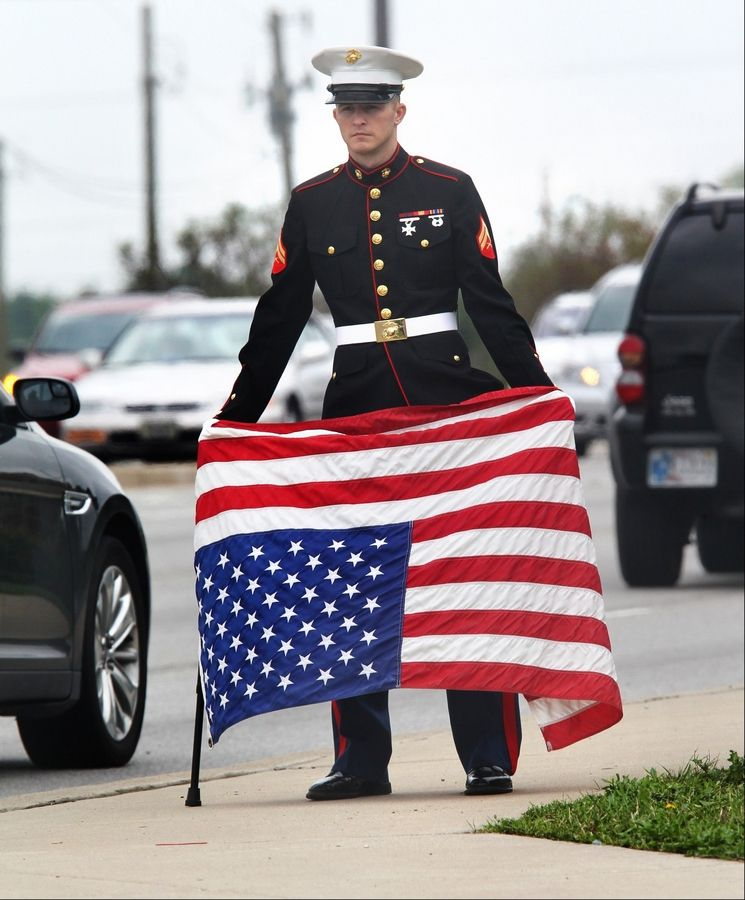 "Beech Grove, Ind. resident Joseph Lohman, 25, who served as a corporal in the U.S. Marines from 2008-2012, shows his concern over the government shutdown by holding an American flag upside down, a signal of distress, just north of I-465, where he has been since midnight. Lohman, who was disabled from a fall in training, is concerned about veterans not getting their disability checks. ""I'm not protesting,"" says Lohman, ""I'm just standing for what is right."""