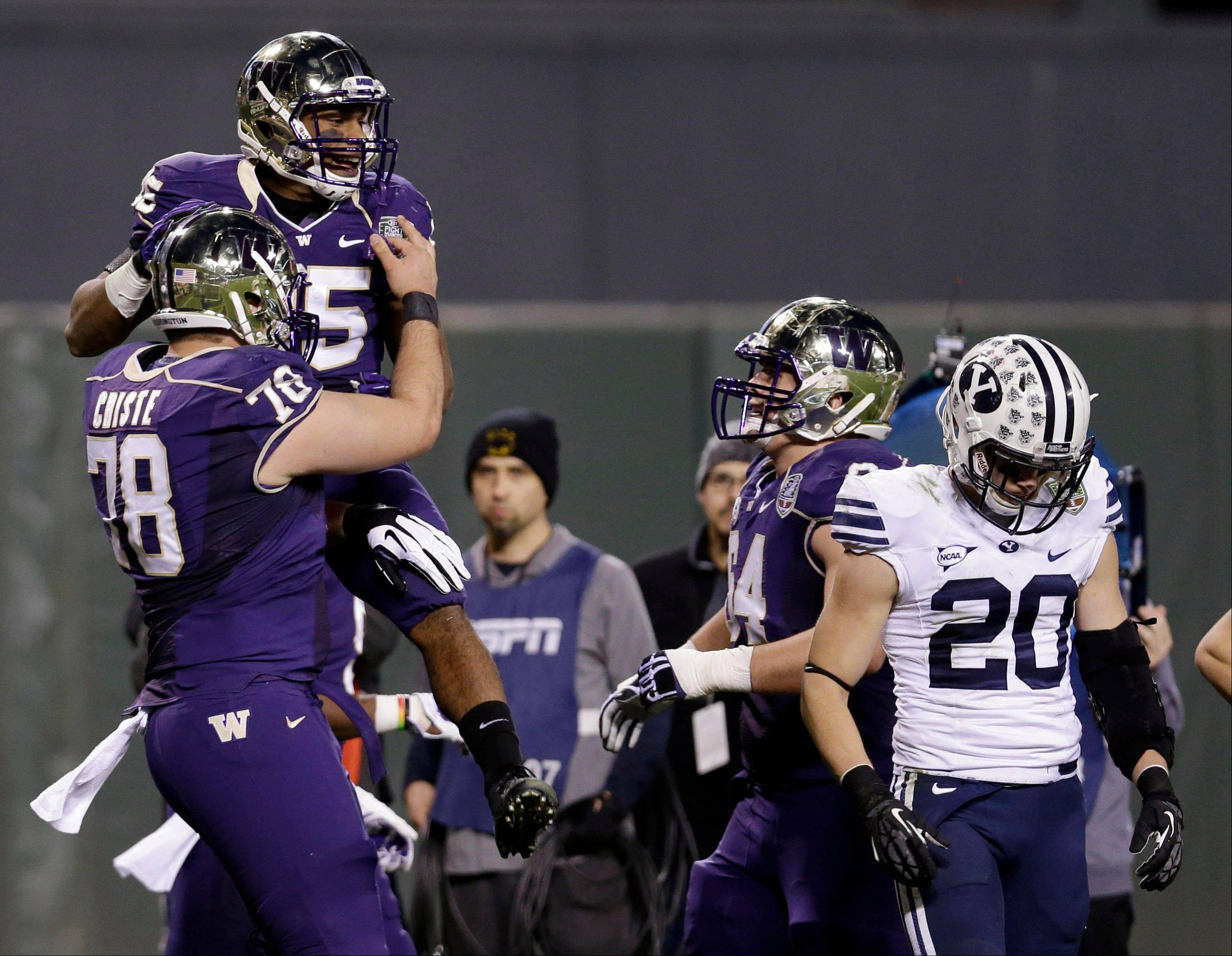 Washington running back Bishop Sankey gets a lift from teammate Mike Criste after rushing for a touchdown against BYU during first half of the Fight Hunger Bowl on Friday in San Francisco.