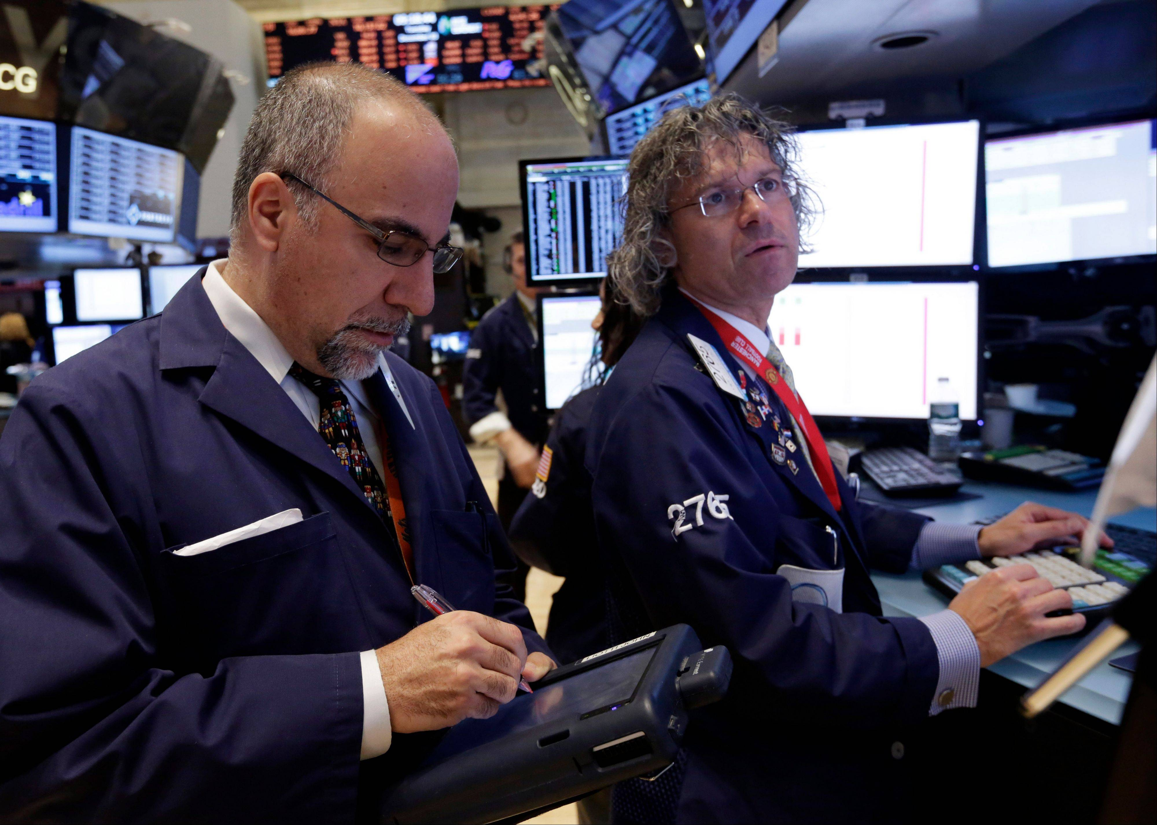 Trader John Liotti, left, and specialist Donald Civitanova work on the floor of the New York Stock Exchange.