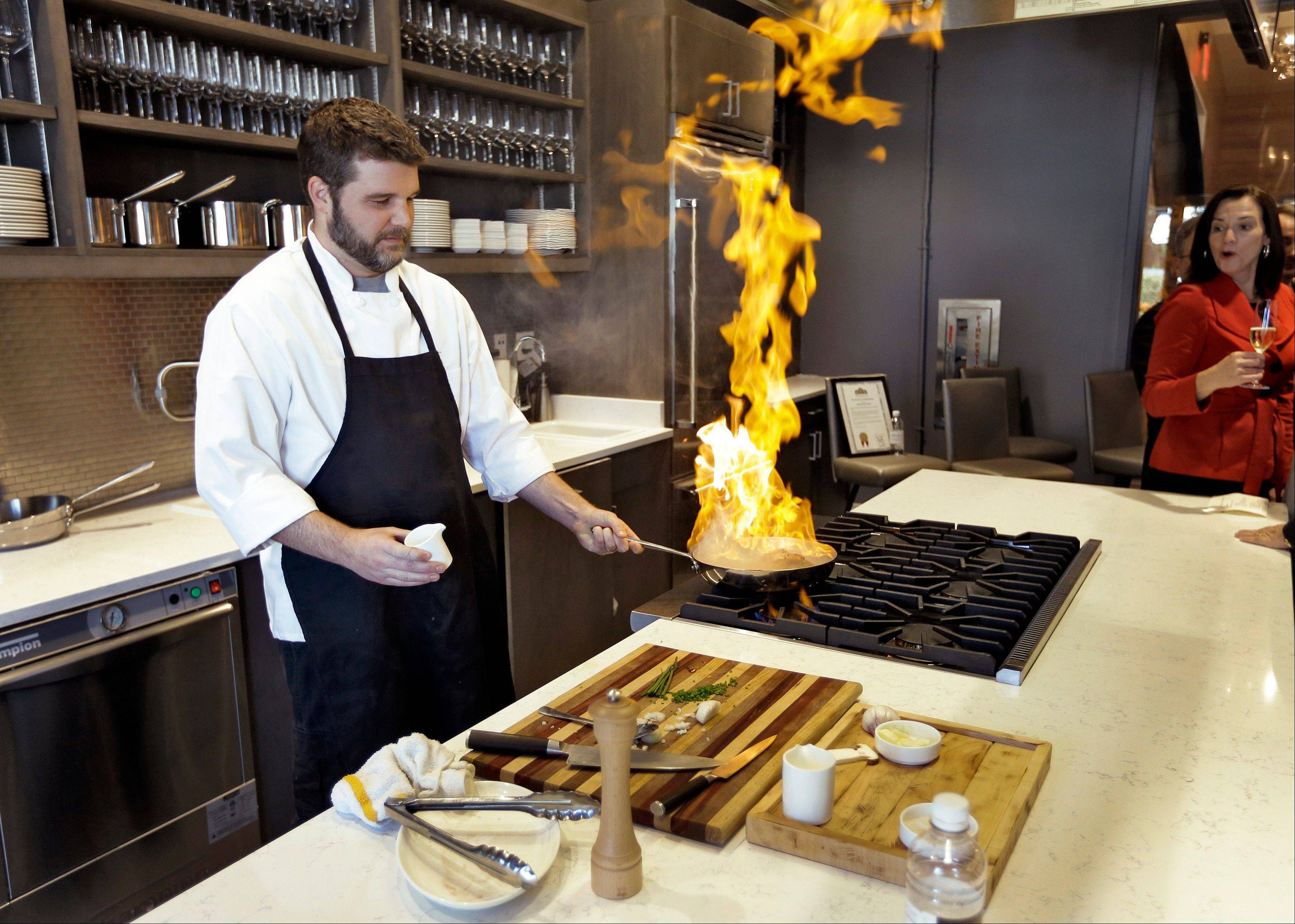 Executive chef Chad Johnson cooks a steak during a tour of the new Epicurean Hotel in Tampa, Fla. Tampa's newest hotel is focused on food, with a restaurant, bakery, culinary theater, wine store and cooking classes on-site.