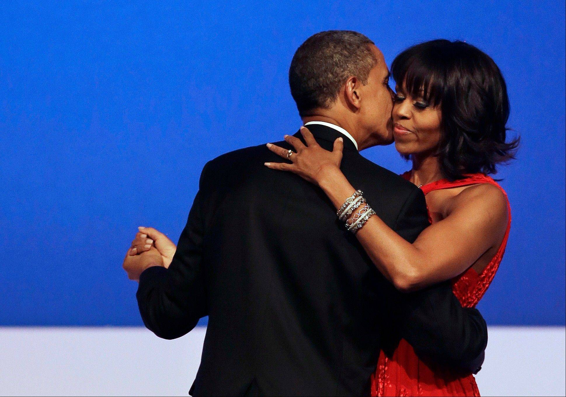 This Jan. 21, 2013 file photo shows President Barack Obama kissing first lady Michelle Obama during their dance at the Commander-in-Chief Inaugural Ball at the Washington Convention Center in Washington. Nobody would call bangs a new trend, but when the first lady's involved, things take on more significance. In fact, President Barack Obama did call his wife Michelle's new hairdo the most significant event of his second inauguration.
