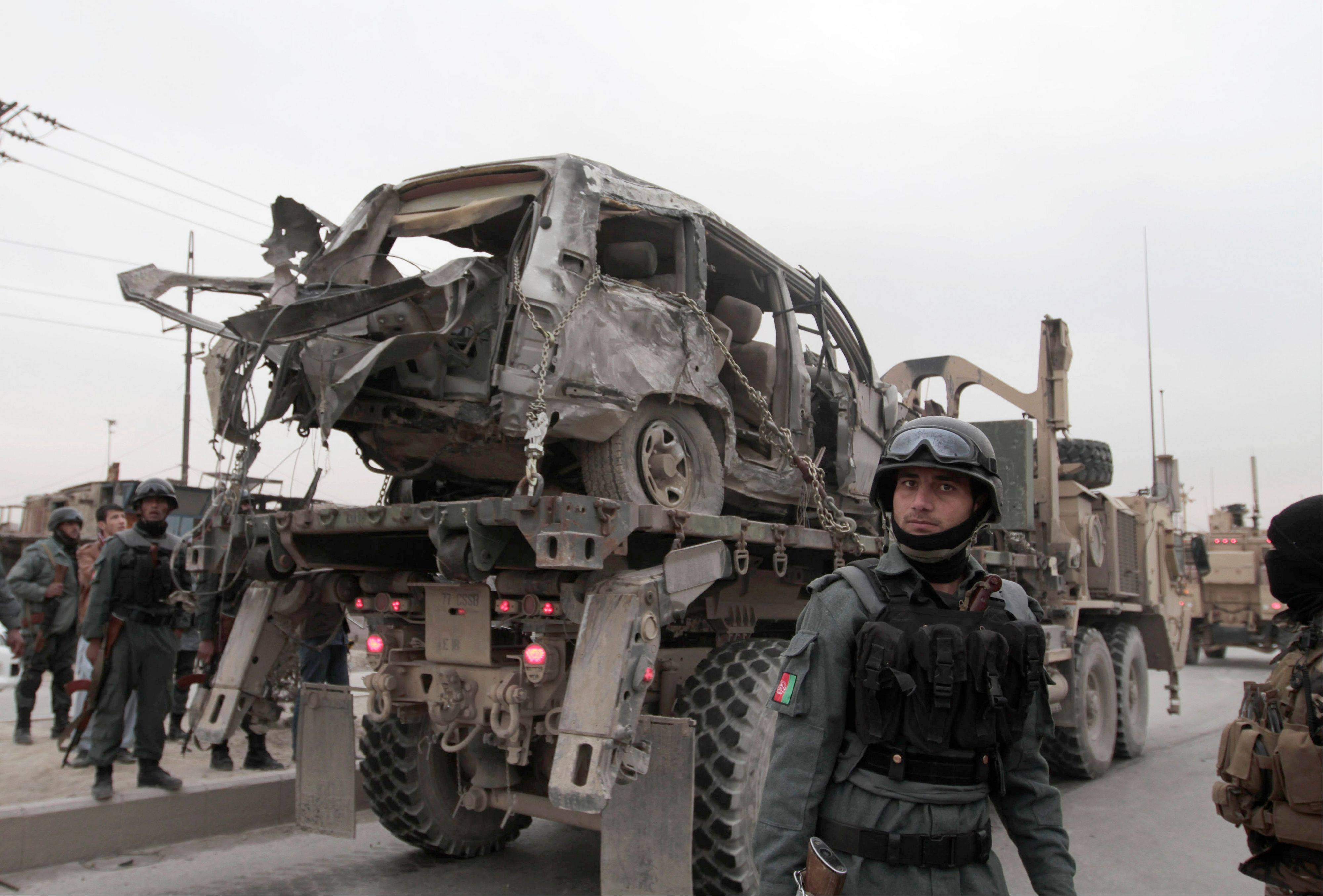 A U.S. military wrecker carries away a vehicle that was destroyed in a suicide car bomb attack on the Jalalabad-Kabul road in Kabul, Afghanistan, Friday. The U.S.-led coalition in Afghanistan says several service members were killed Friday when a suicide car bomber attacked their convoy in an eastern district of the capital, Kabul.