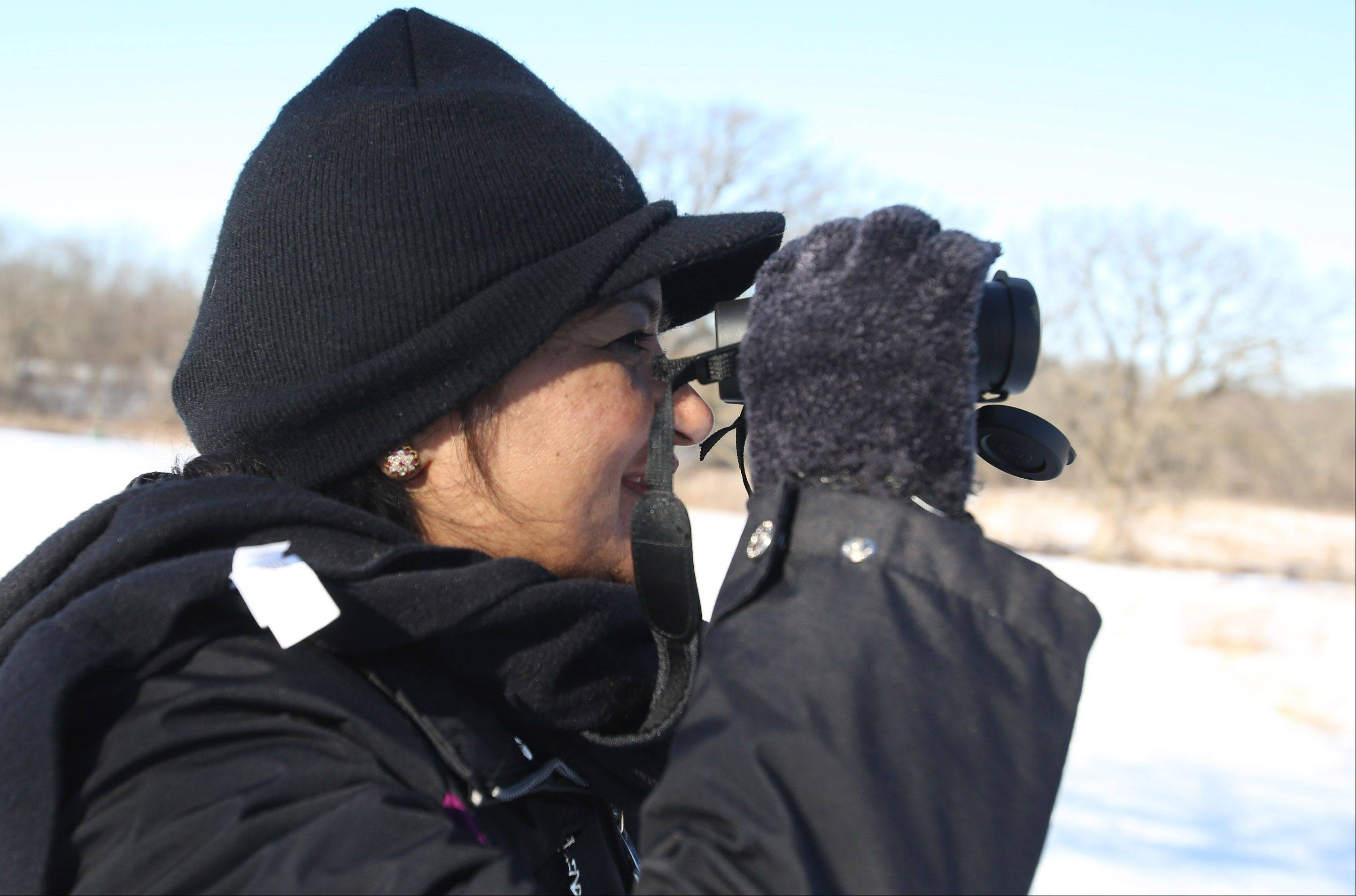 Kamini Mac of Aurora uses binoculars to spot birds near Creek Bend Nature Center during a Winter Birds program on Saturday in St. Charles.
