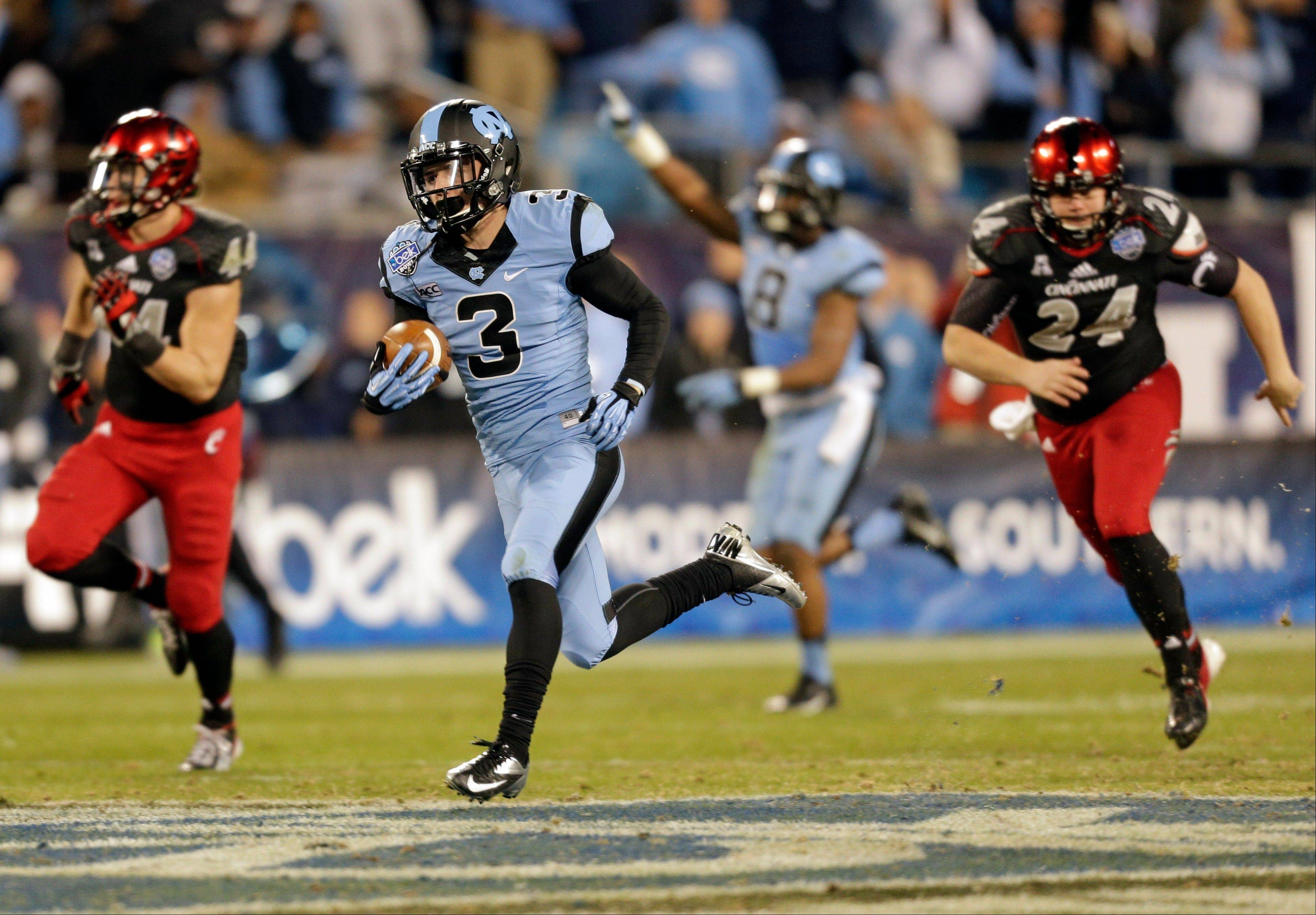 North Carolina's Ryan Switzer (3) returns a punt for a touchdown past Cincinnati's John Lloyd (24) and Corey Mason (44) during the second half of the Belk Bowl NCAA college football game, Saturday, Dec. 28, 2013, in Charlotte, N.C. (AP Photo/Chuck Burton)