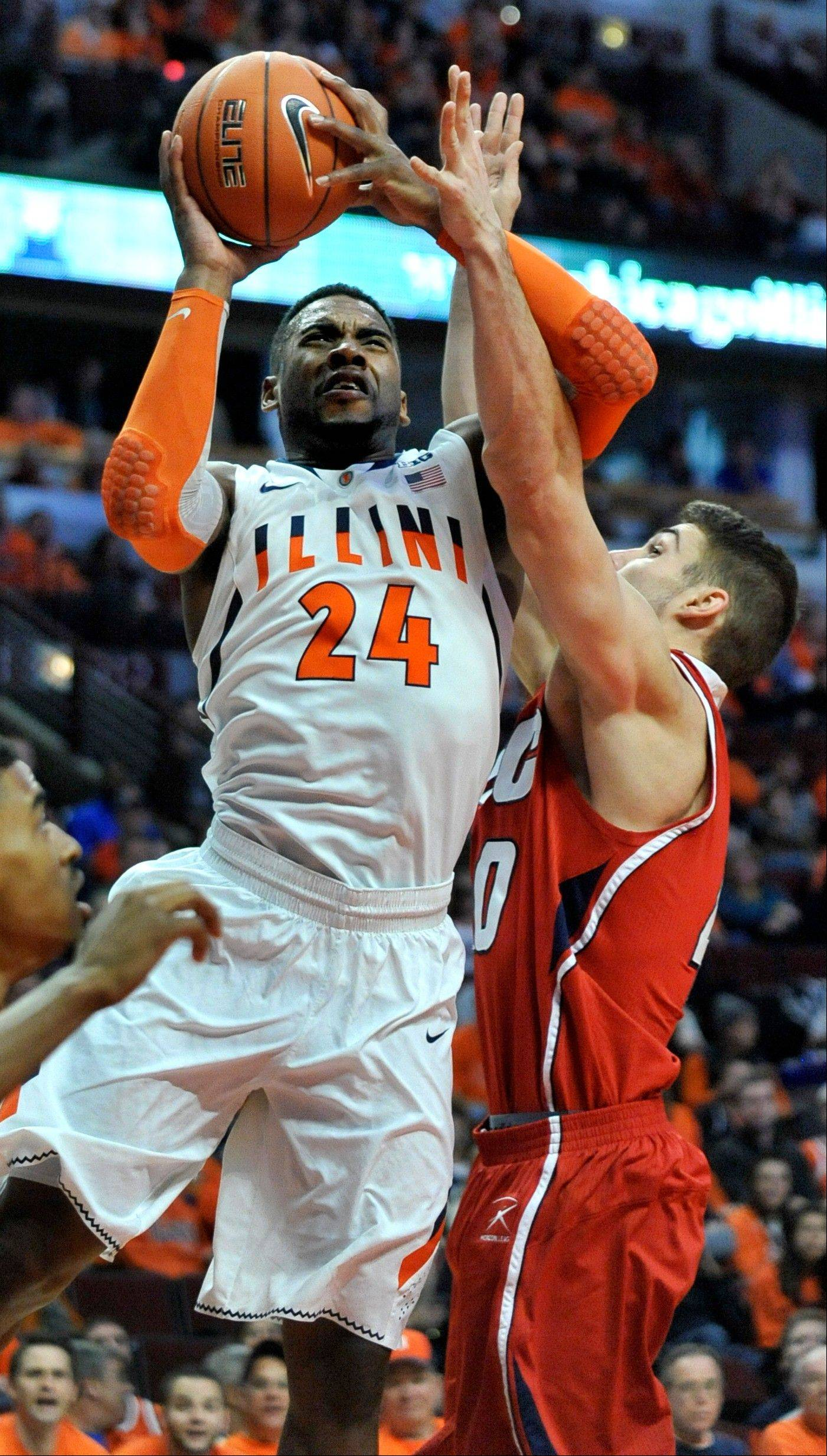 Illinois' Ravonte Rice (24) goes up for a shot against Illinois-Chicago's Jake Wiegeand (40) during the first half of an NCAA college basketball game in Chicago, Saturday, Dec., 28, 2013. (AP Photo/Paul Beaty)