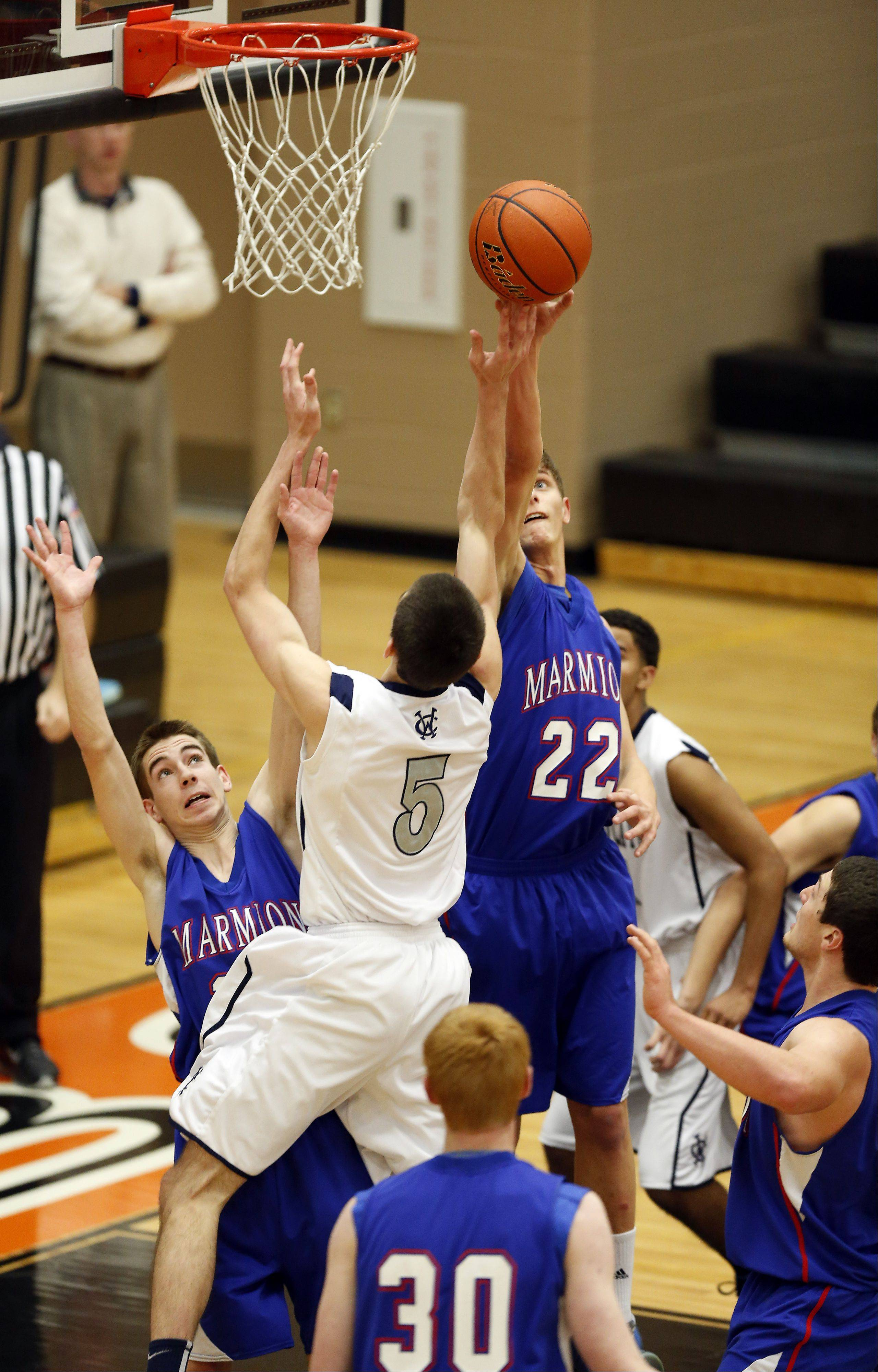 Marmion�s Jake Esp, 22, knocks a shot away from West Chicago�s John Konchar, 5, during the third place game at the 86th Annual Chuck Dayton Holiday Basketball Tournament at Dekalb High School Friday December 27, 2013.