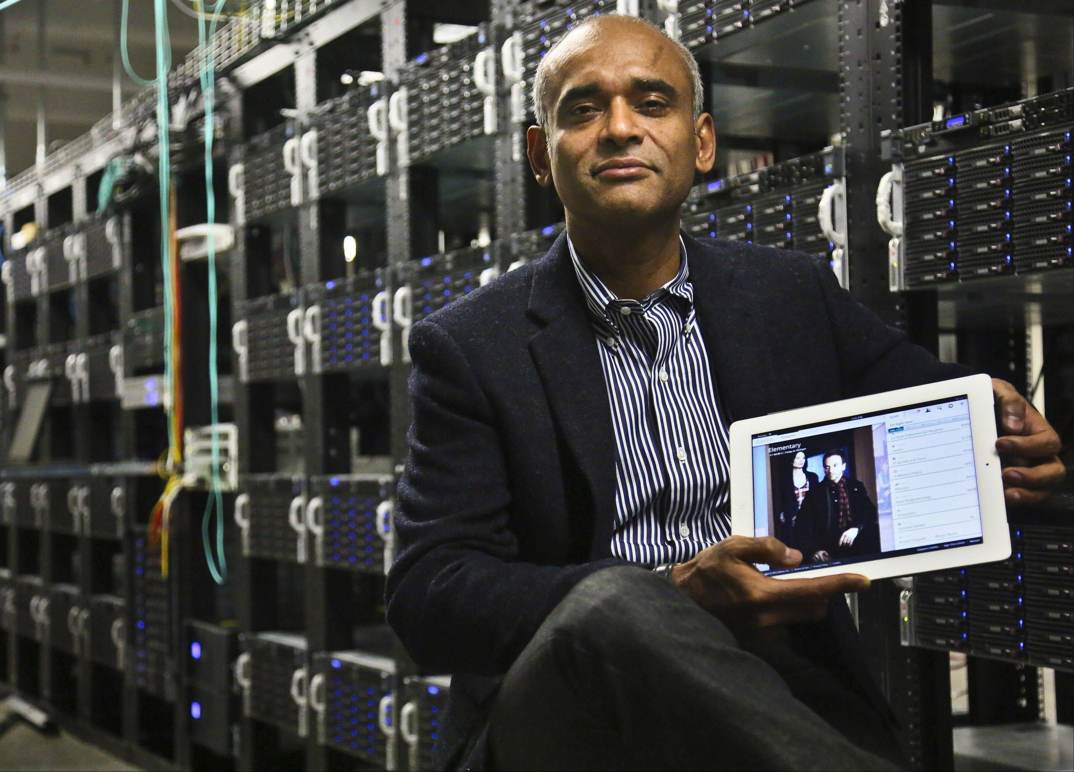 Chet Kanojia, founder and CEO of Aereo, Inc., shows a tablet displaying his company's technology, in New York. Aereo is one of several startups created to deliver traditional media over the Internet without licensing agreements.