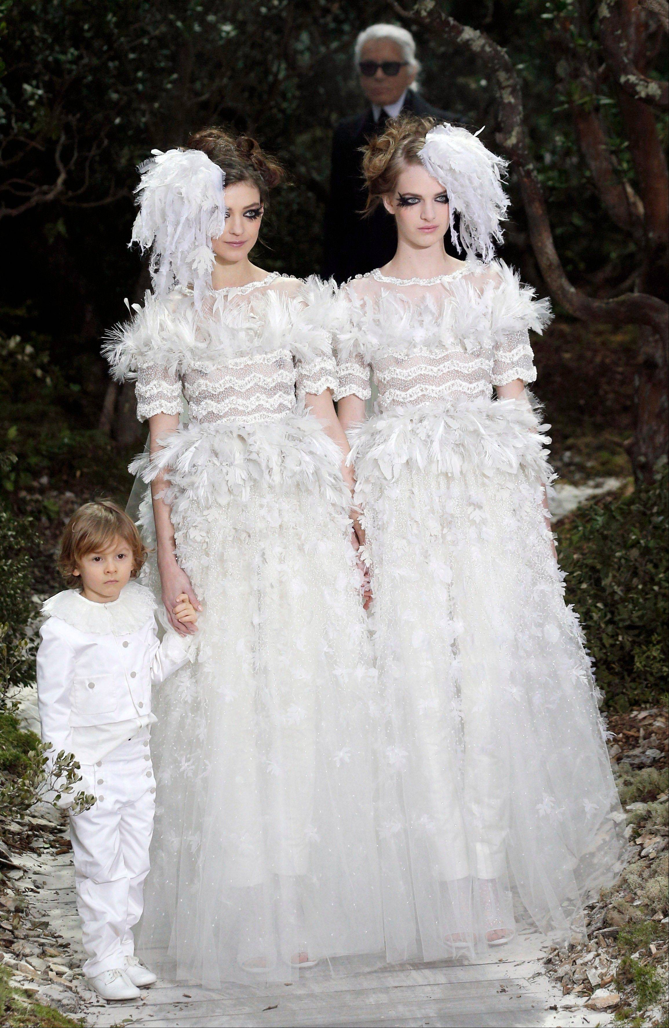 This Jan. 22, 2013 file photo shows two models wear wedding gowns by German fashion designer Karl Lagerfeld for Chanel's Spring Summer 2013 Haute Couture fashion collection, in Paris. Lagerfeld used fashion to support a controversial French gay marriage law, sending two brides together down the catwalk.