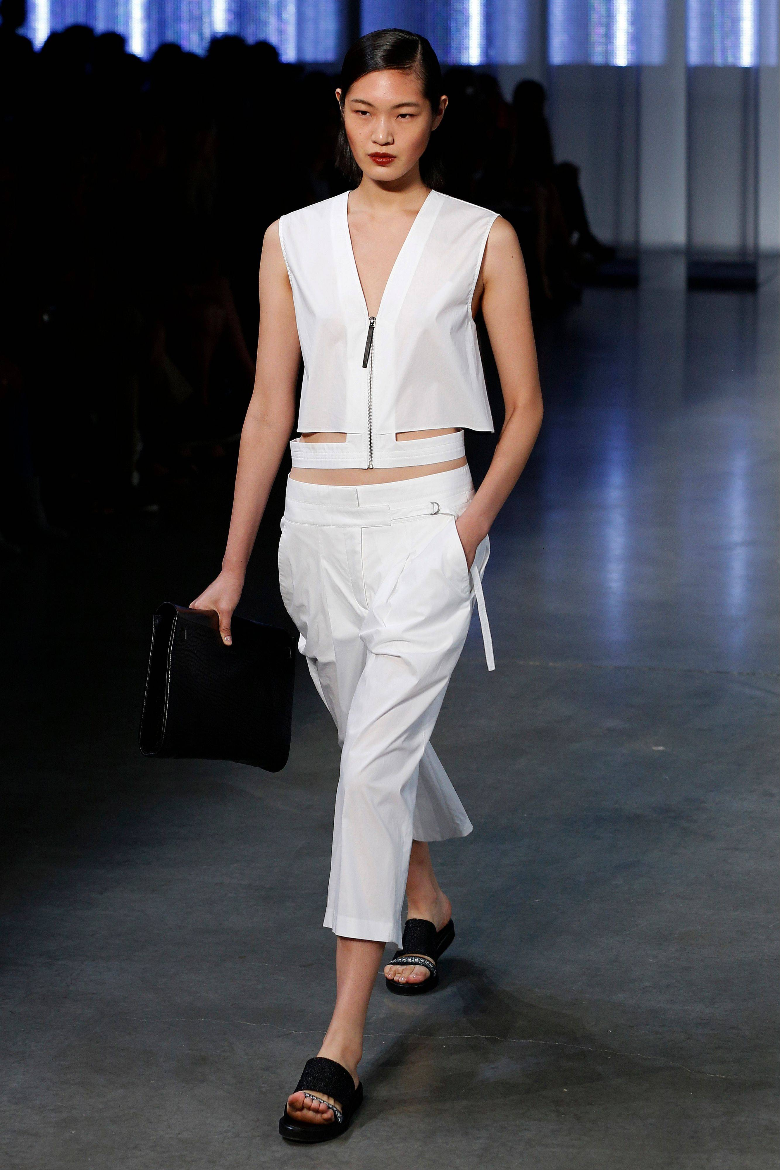 This Sept. 6, 2013 file photo shows a model wearing sandals as she models the Helmut Lang Spring 2014 collection during Fashion Week in New York. In shoe stores this year, you could see a trend toward flats, including a notable reinterpretation of those chunky Birkenstocks.