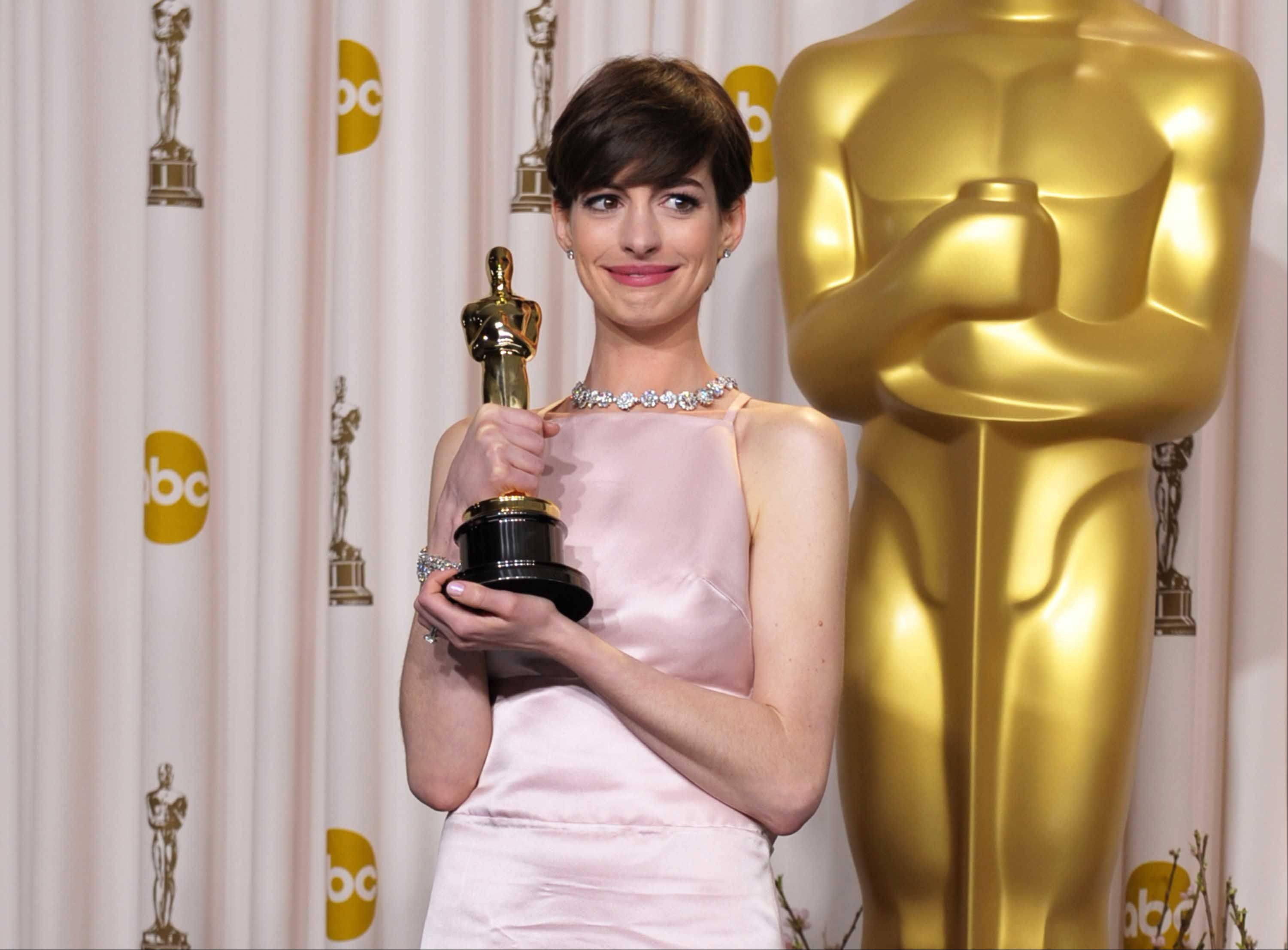 "This Feb. 24, 2013 file photo shows Anne Hathaway sporting a pixie haircut at as she poses with her award for best actress in a supporting role for ""Les Miserables"" during the Oscars in Los Angeles."
