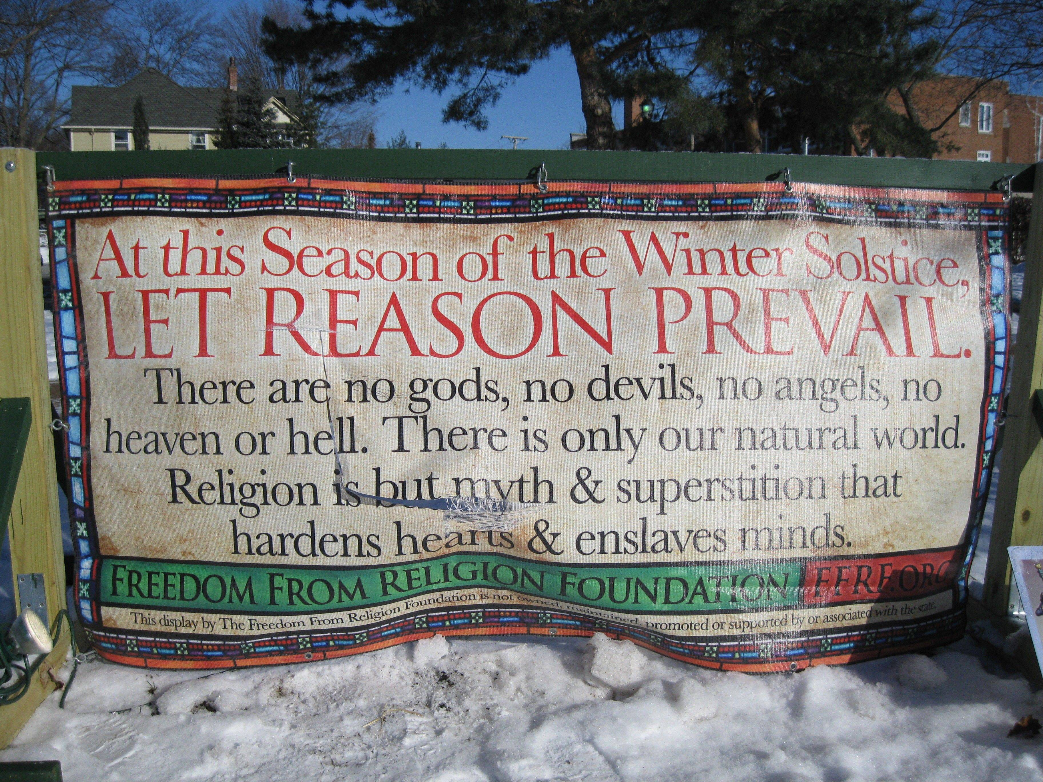 A sign put on display by the Freedom From Religion Foundation in an Arlington Heights park was recently vandalized, police said. This is the second year the group has placed the banner next to a Nativity scene in the public park.