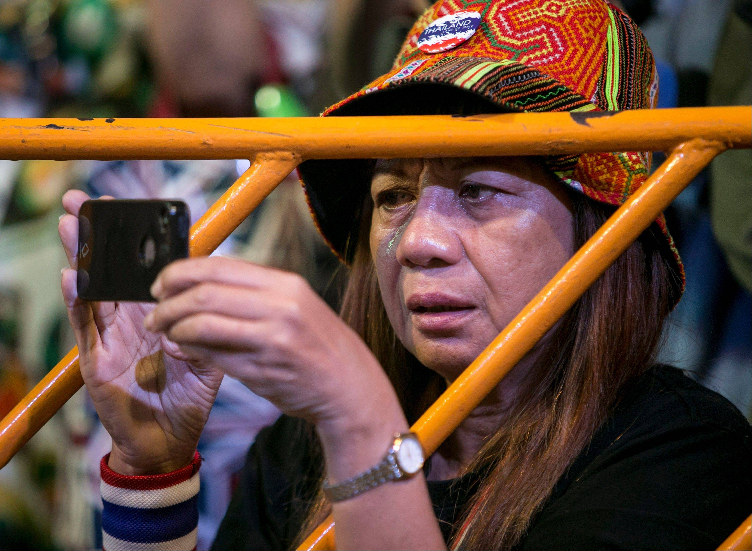 A Thai anti-government protester cries and takes picture during a condolence ceremony for Yuthana Ong-art, who was shot and killed on Friday night, in Bangkok, Thailand. Gunmen killed the anti-government activist and wounded two others in Thailand's capital on Saturday, while protesters elsewhere blocked candidates from registering for upcoming elections, deepening a political crisis that threatens to derail democracy in the Southeast Asian nation.