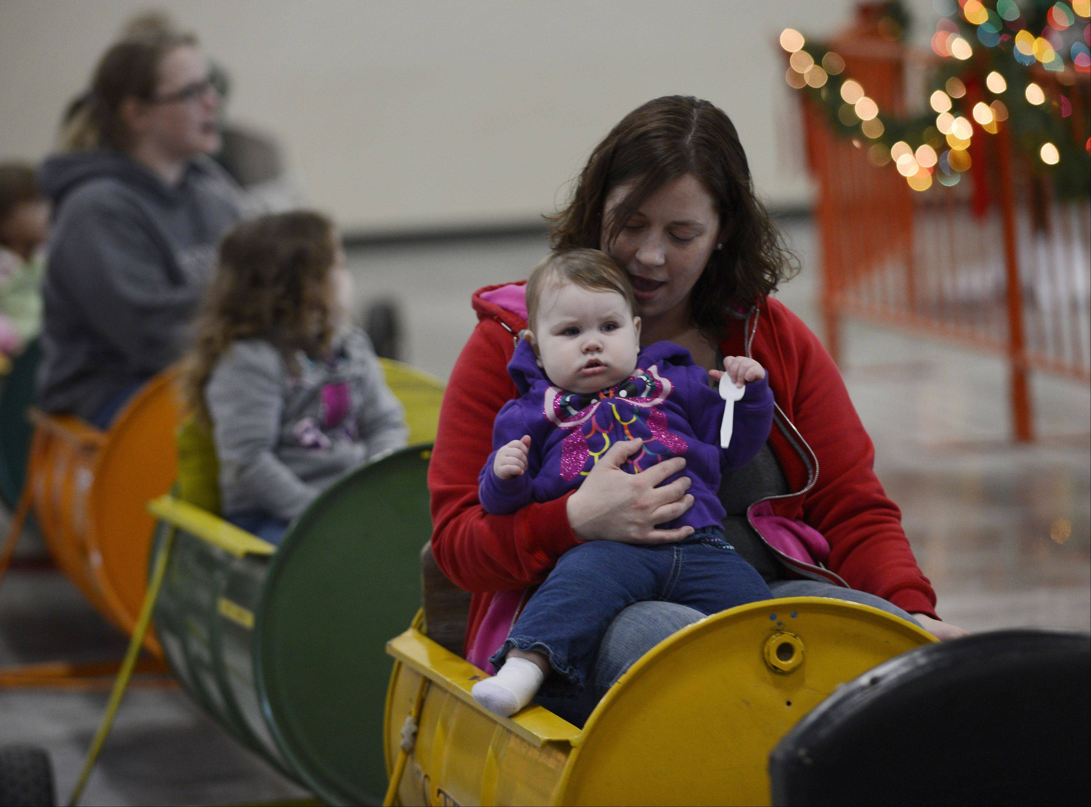 Avri Beck, age 10 months, of Round Lake Beach, rides the barrel train with her mom Rebekah during the Holiday Hoedown at the Lake County Fairgrounds Saturday. The event continues today.