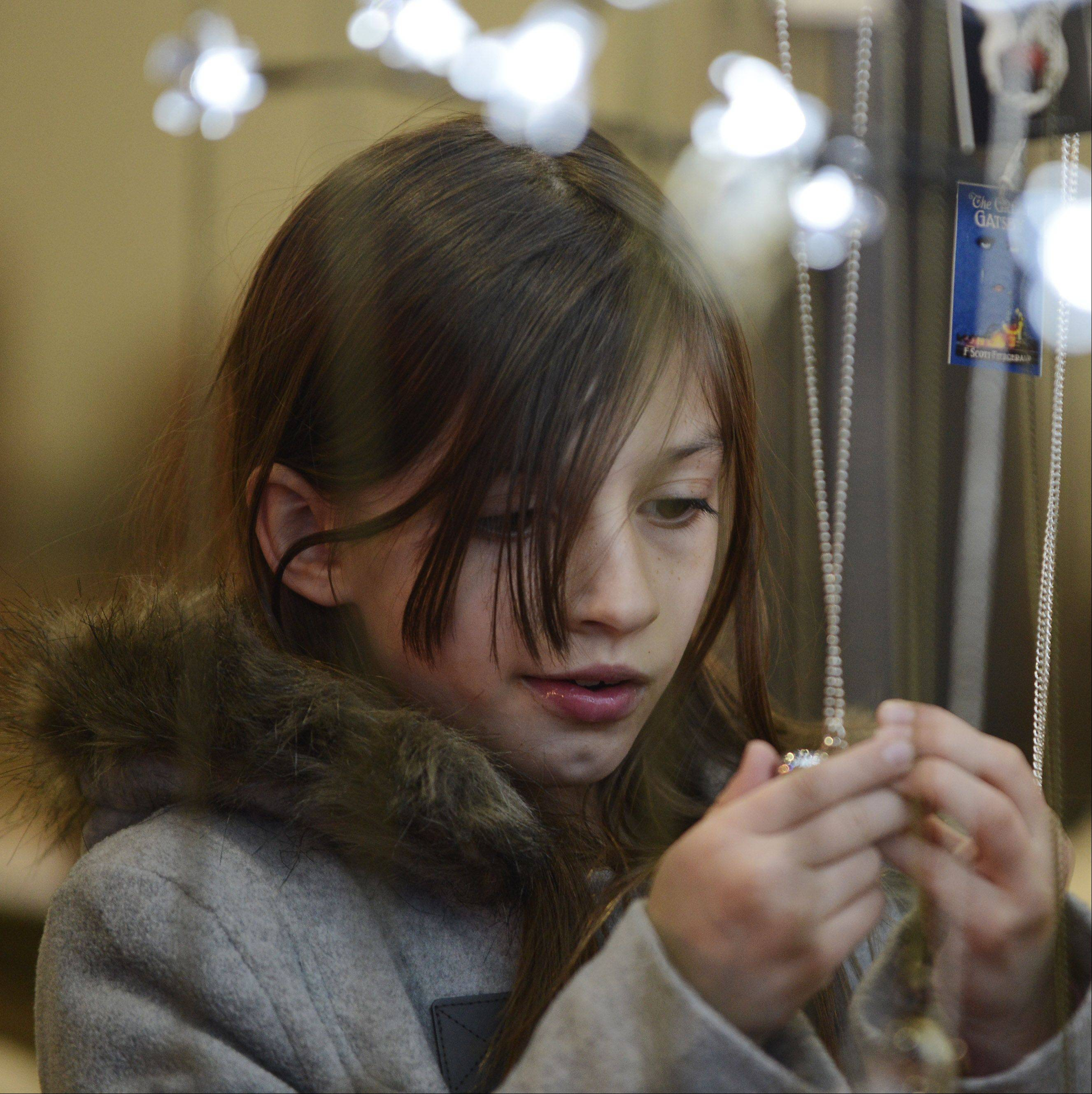 Madison Leaman, 8, of Woodstock views jewelry items displayed by a merchant during the Holiday Hoedown at the Lake County Fairgrounds Saturday. The event continues today.