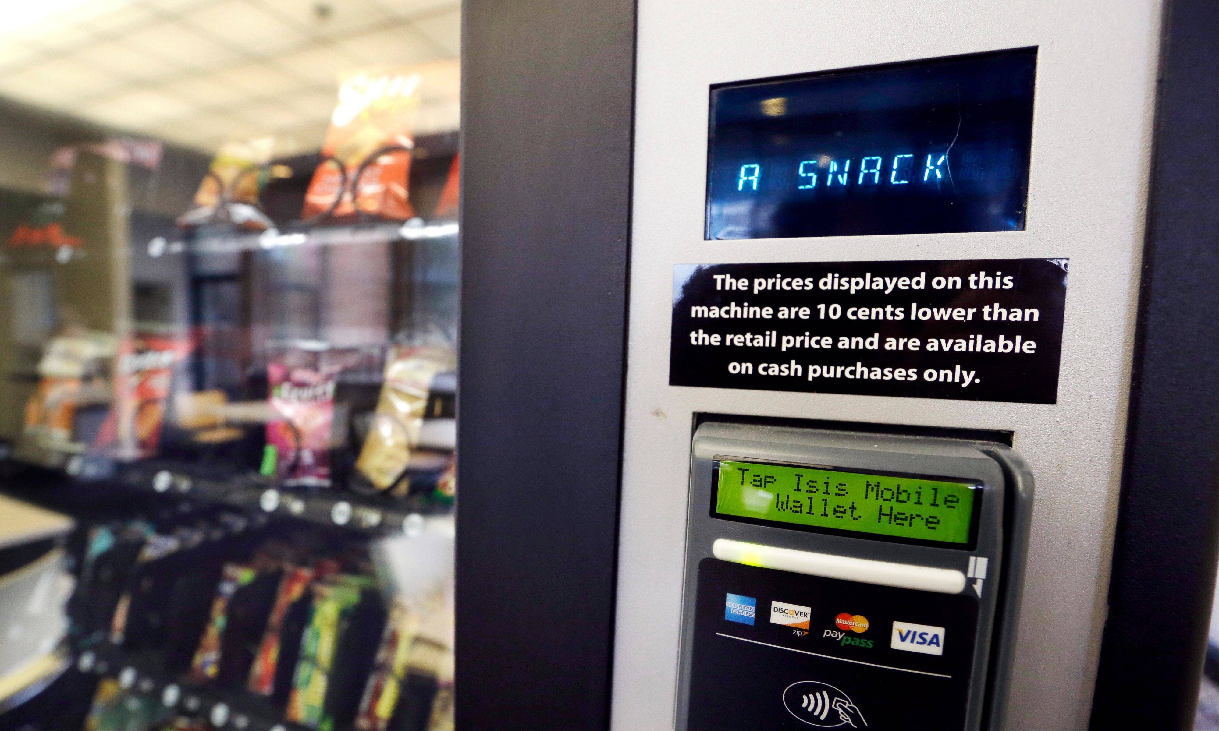 In this Dec. 23, 2013 photo, a vending machine advertises snacks on a small screen on the machine in Seattle. Office workers in search of snacks will be counting calories along with their change under new labeling regulations for vending machines included in President Barack Obama's health care overhaul law. The Food and Drug Administration, which is expected to release final rules early next year, says requiring calorie information to be displayed on roughly 5 million vending machines nationwide will help consumers make healthier choices.