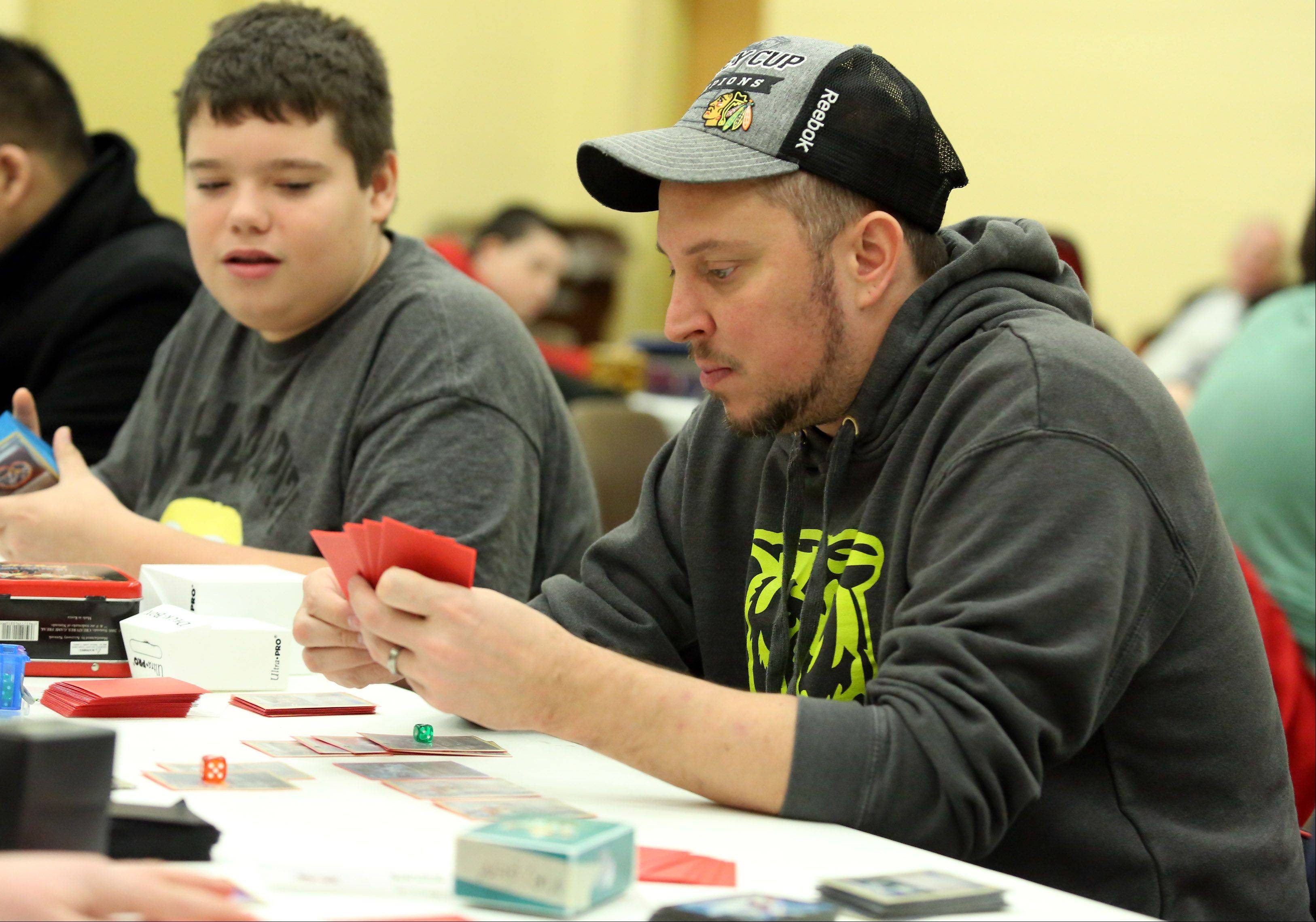 Pok�mon City Championships organizer Jimmy Ballard of Plainfield, right, said the competition is like playing chess with cards as 60 competed at the Huntley Park District on Saturday.