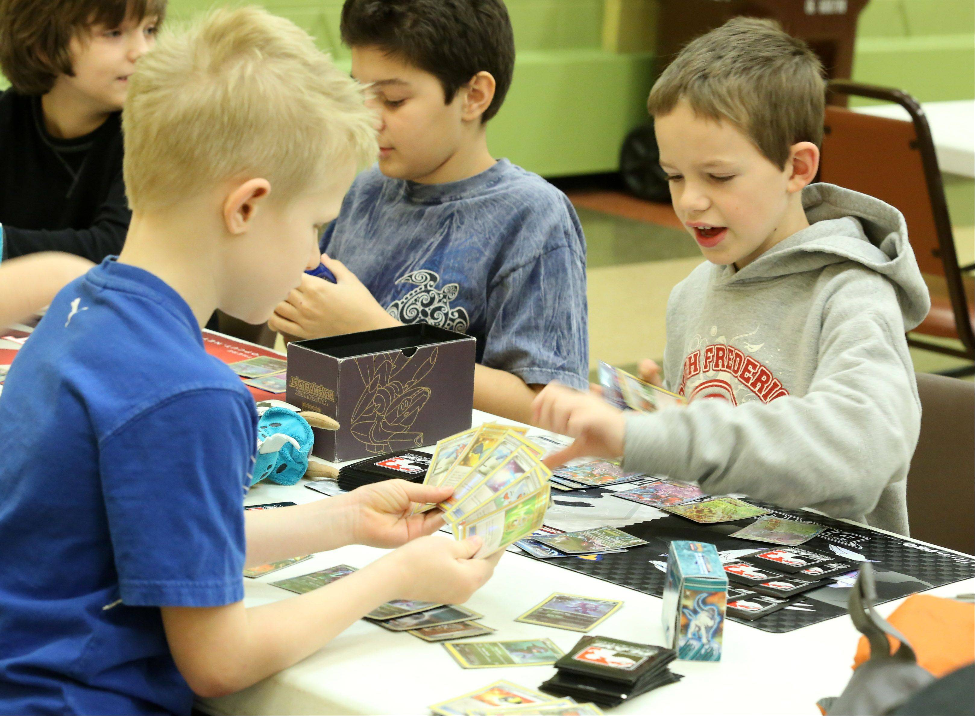 Samuel Bruce, 9, of Mundelein, right, plays Easton Ours, 8, of Naperville during the Pokémon City Championships at the Huntley Park District on Saturday in Huntley.