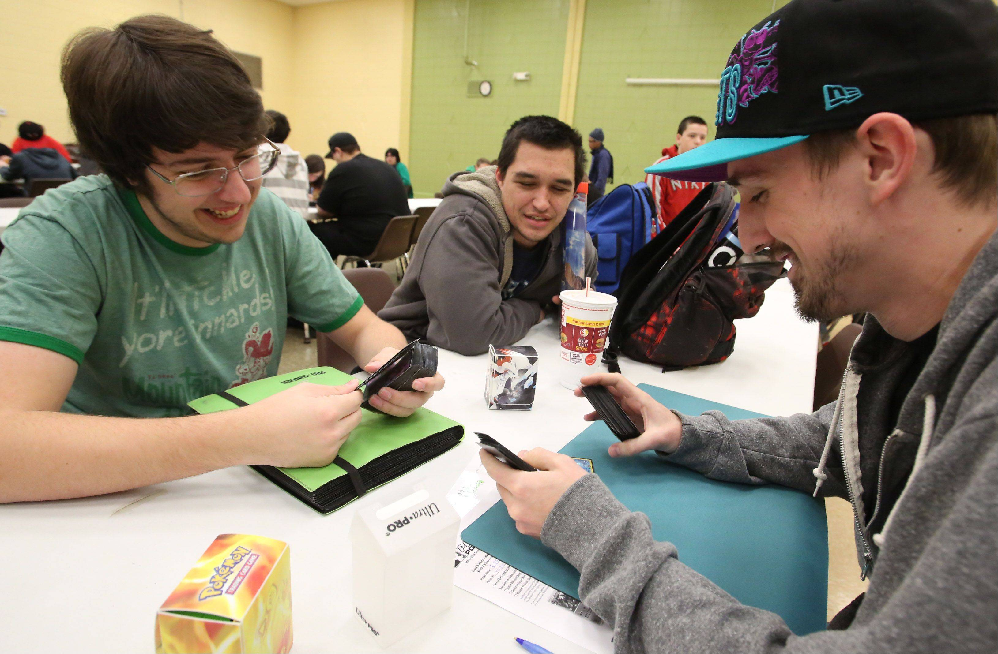Steven Vlosak, of Downers Grove, left, prepares to play Drew Stasica of Oswego, as Cody Kiessmann of Westmont looks on during the Pokémon City Championships at the Huntley Park District on Saturday.