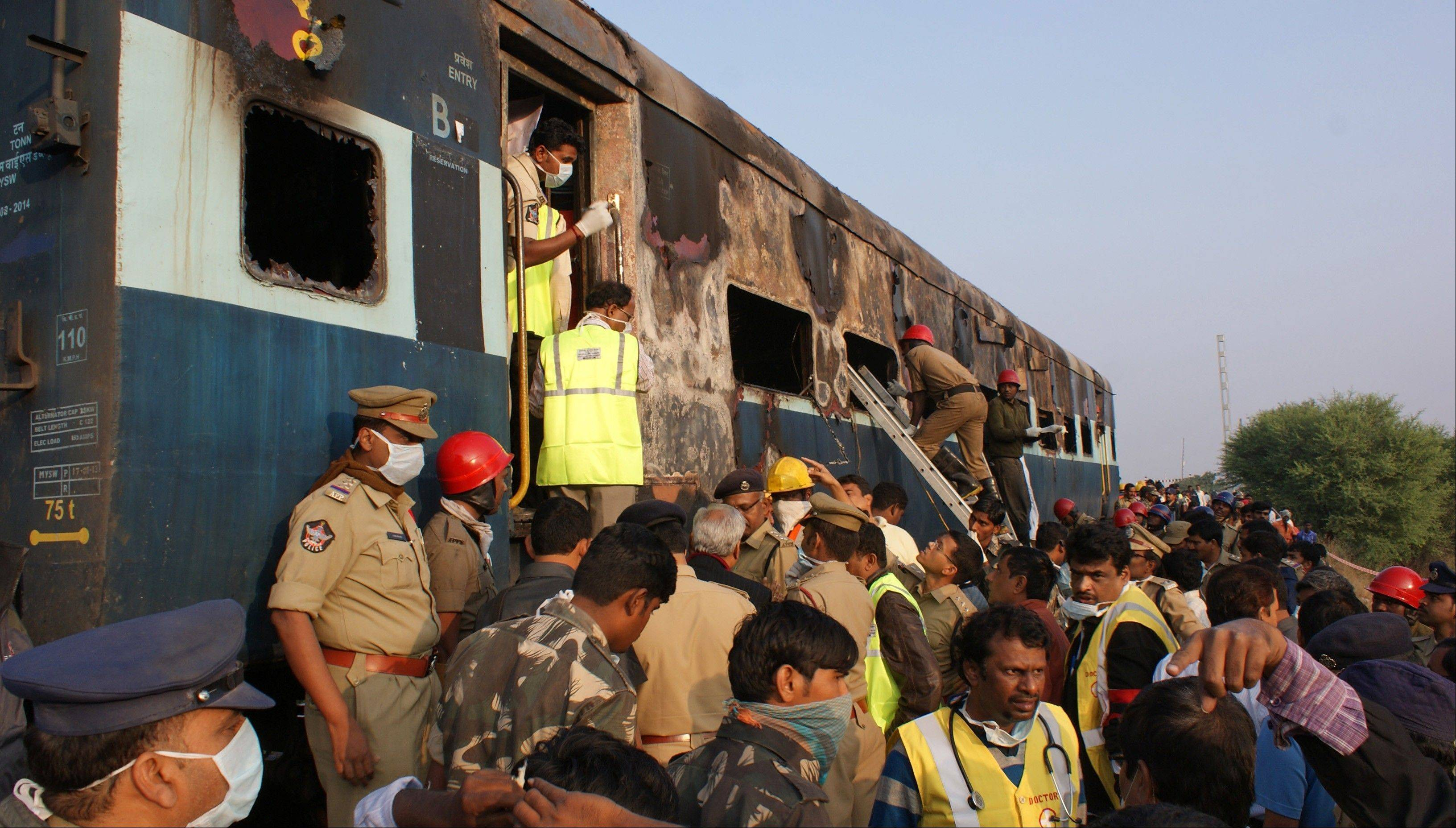 Associated PressPoliceman and firefighters search for victims of a train accident at Kothacheruvu, about 96 miles north of Bangalore, India, Saturday, Dec. 28. A fire engulfed two coaches of an express train in southern India early Saturday, killing at least two dozen, many of whom became trapped and suffocated after the doors failed to open, officials said.
