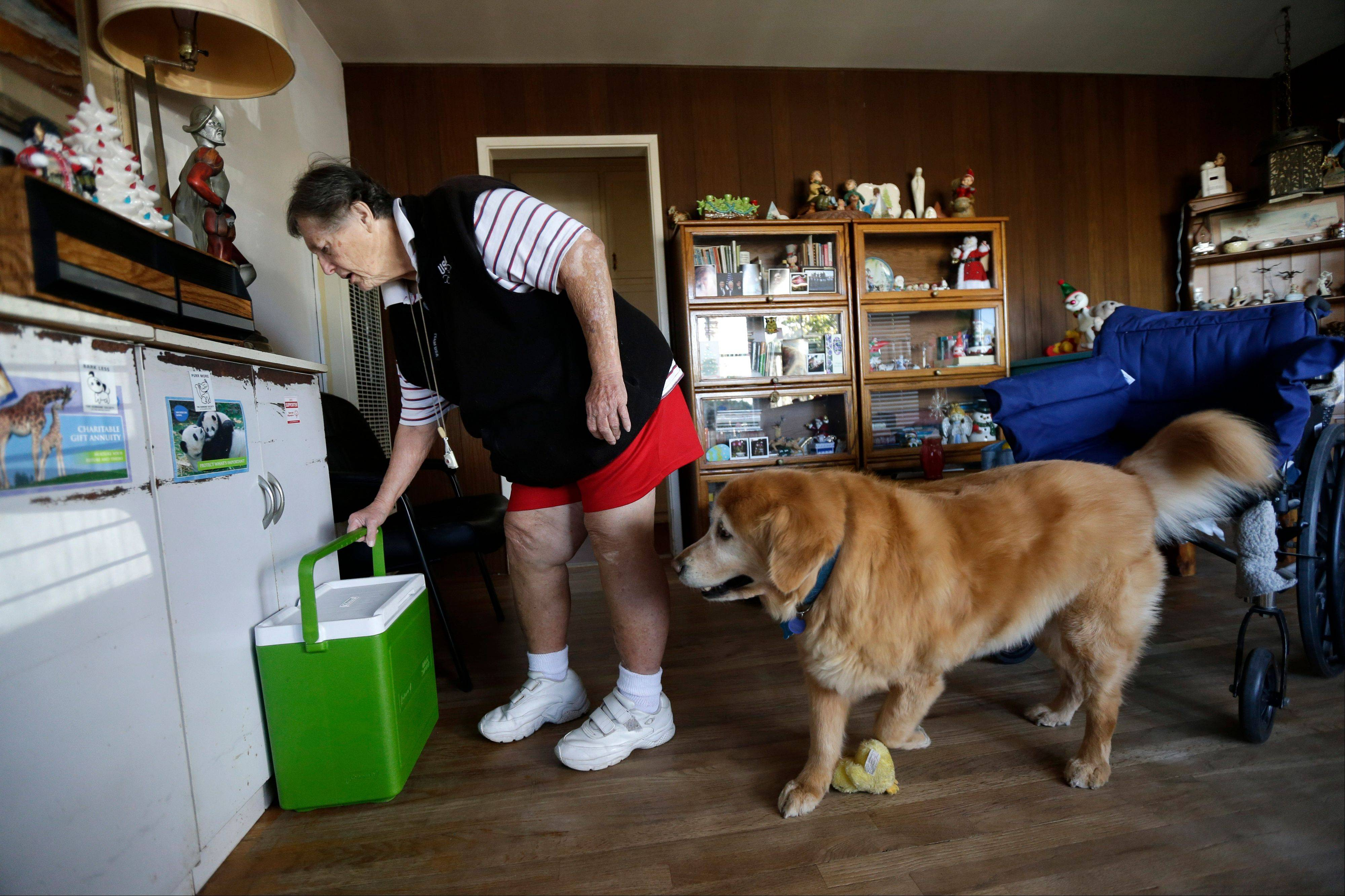 Sherry Scott moves a cooler holding her Meals on Wheels as her 10-year-old golden retriever Tootie looks on at her home in San Diego. Scott, who receives dog food for Tootie through the Animeals program, said she would give her lasagna and pork riblets from Meals on Wheels to Tootie if MOW didn't bring dog food for the dog. The pet food program is sponsored by the Helen Woodward Animal Center.